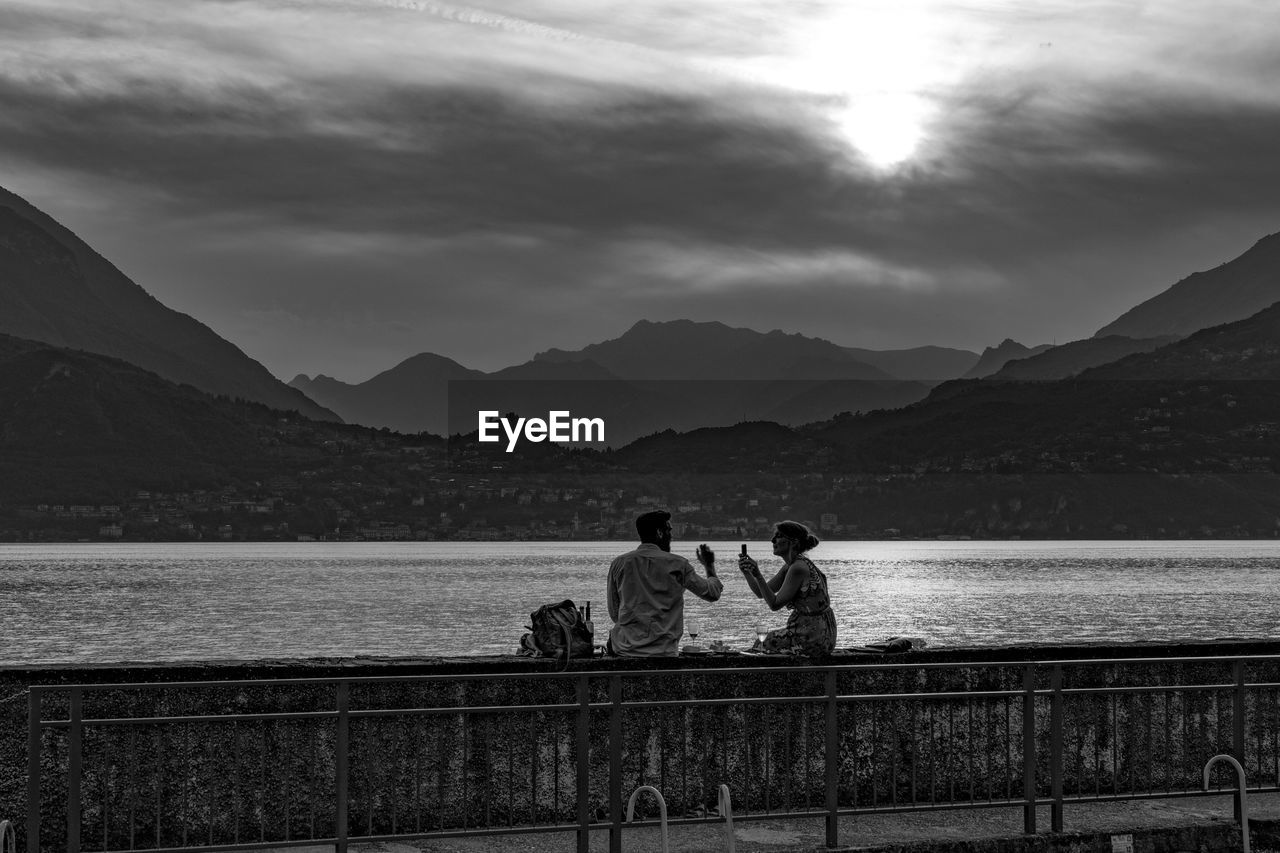 mountain, water, sky, real people, leisure activity, two people, mountain range, nature, beauty in nature, men, women, cloud - sky, lifestyles, togetherness, scenics - nature, rear view, lake, adult, railing, couple - relationship, outdoors, positive emotion, looking at view