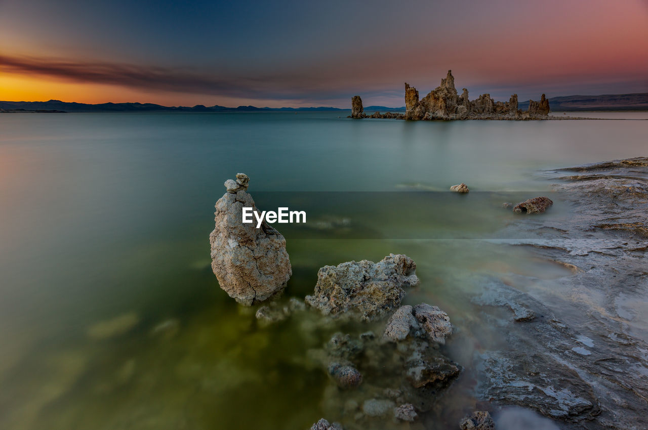 Rock formations in mono lake against sky at sunset