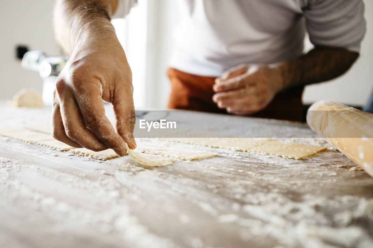 indoors, selective focus, dough, human hand, preparation, senior adult, food and drink, midsection, human body part, men, real people, table, senior men, home interior, kneading, kitchen, occupation, togetherness, standing, freshness, day, people