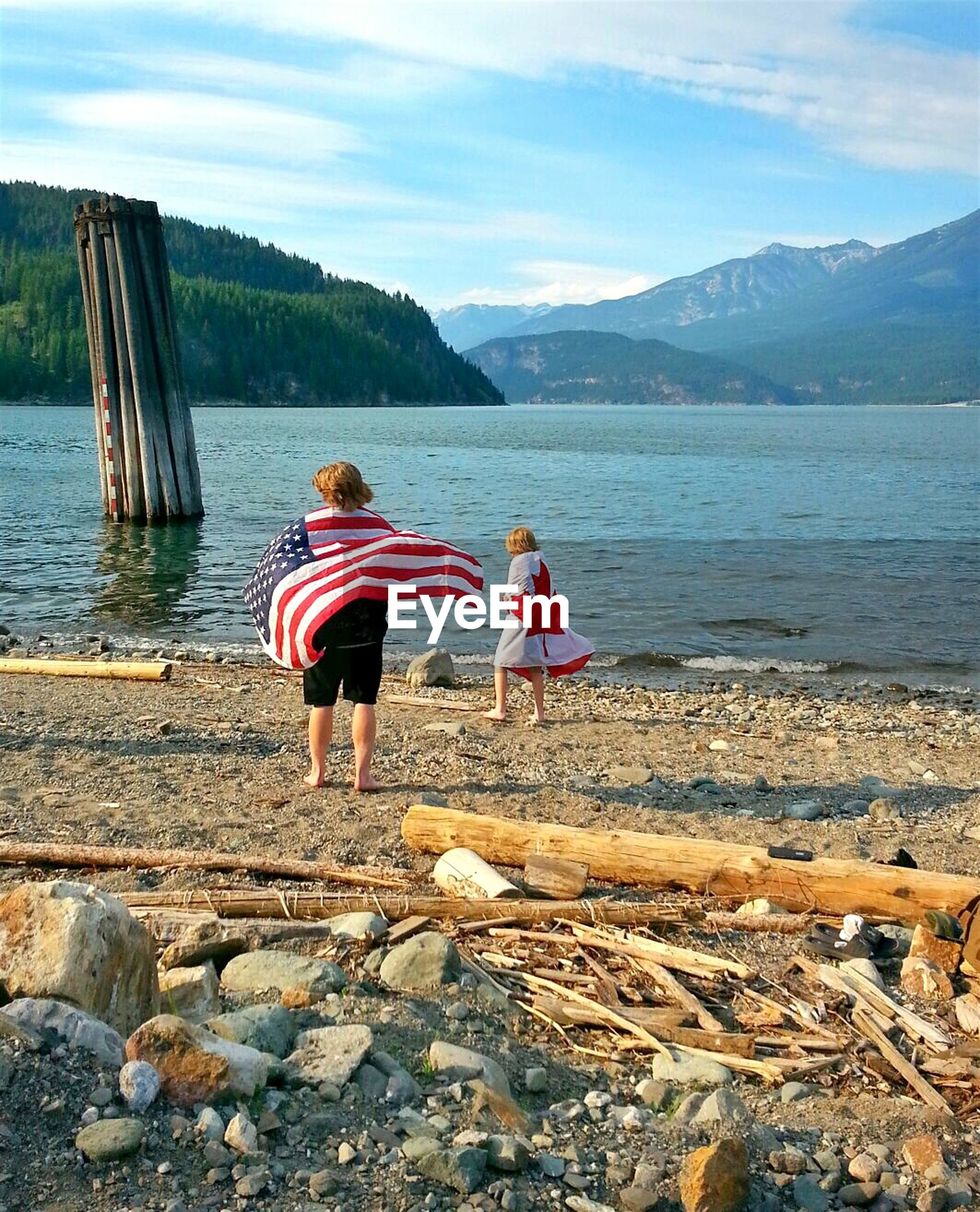 REAR VIEW OF TWO MEN ON SHORE