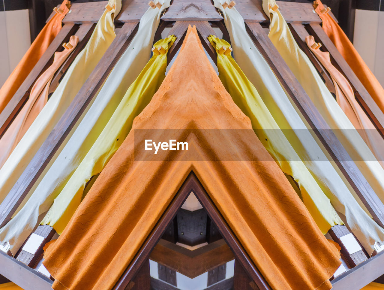 no people, pattern, low angle view, built structure, close-up, design, architecture, indoors, yellow, day, full frame, shape, backgrounds, wood - material, multi colored, building, orange color, hanging, wall - building feature, ceiling