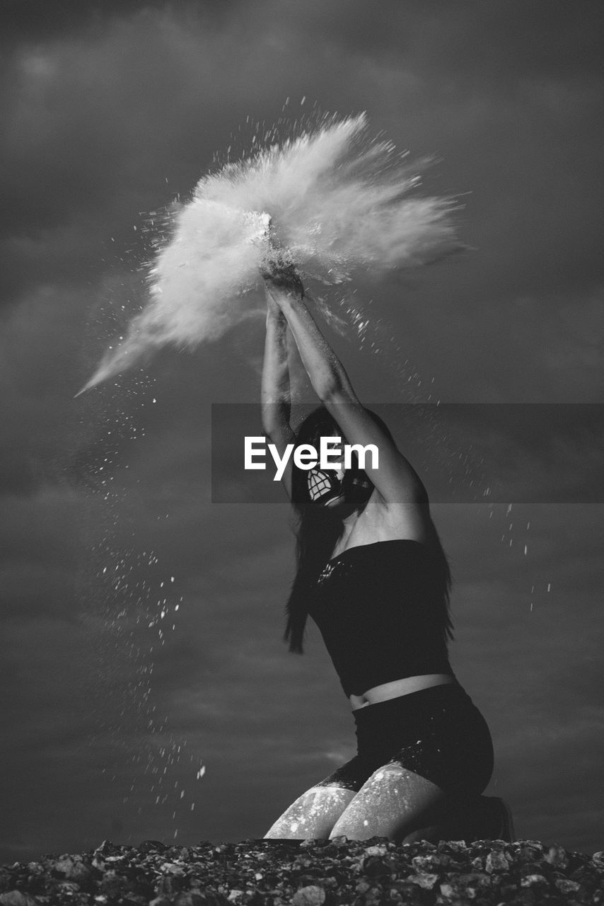 Young woman splashing powder against sky