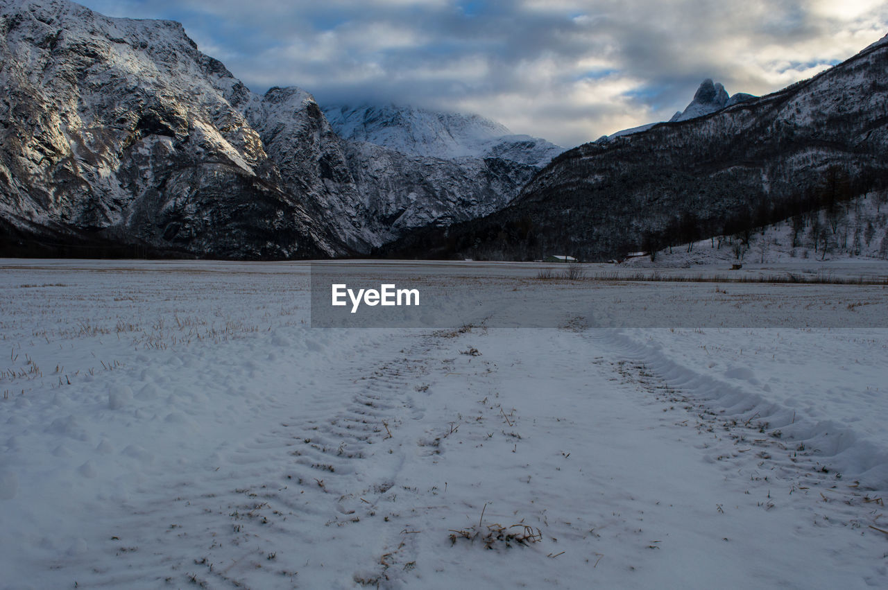 Snow covered field against mountains