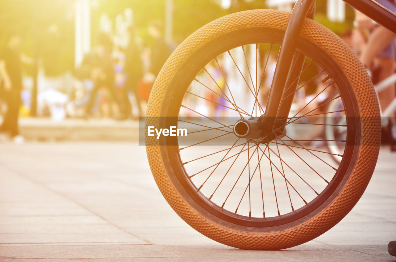 wheel, focus on foreground, transportation, bicycle, land vehicle, close-up, sunlight, mode of transportation, street, spoke, no people, outdoors, tire, day, city, footpath, wood - material, nature, stationary, yellow