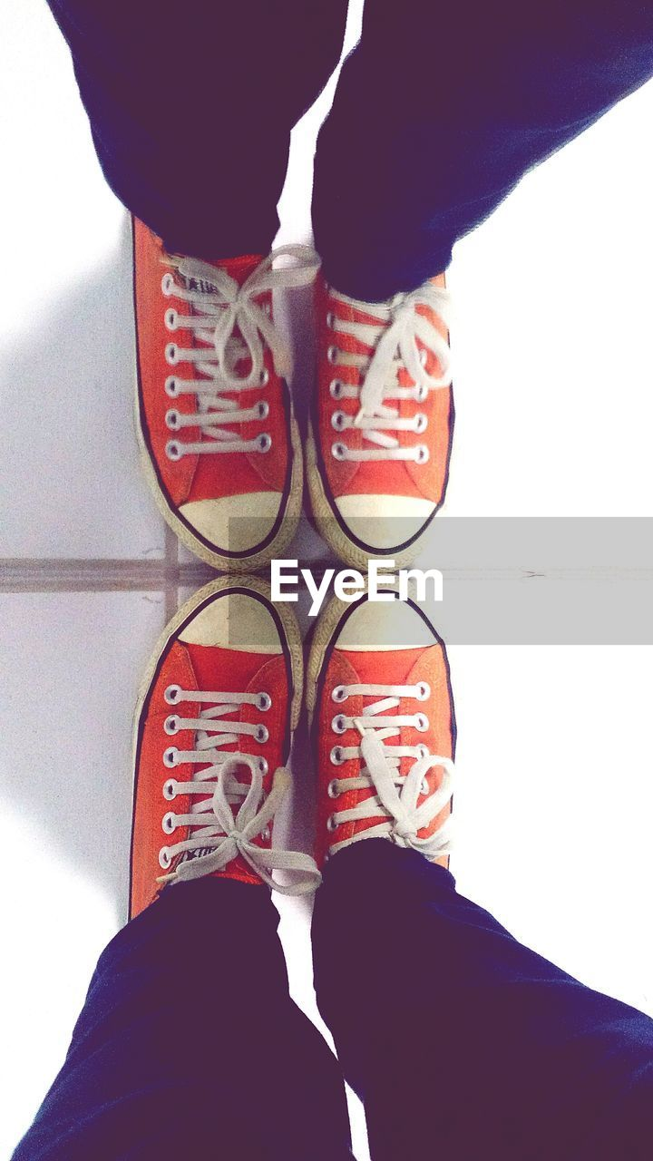 low section, human leg, shoe, real people, standing, one person, human foot, human body part, personal perspective, high angle view, lifestyles, indoors, canvas shoe, men, pair, leisure activity, day, women, close-up, people