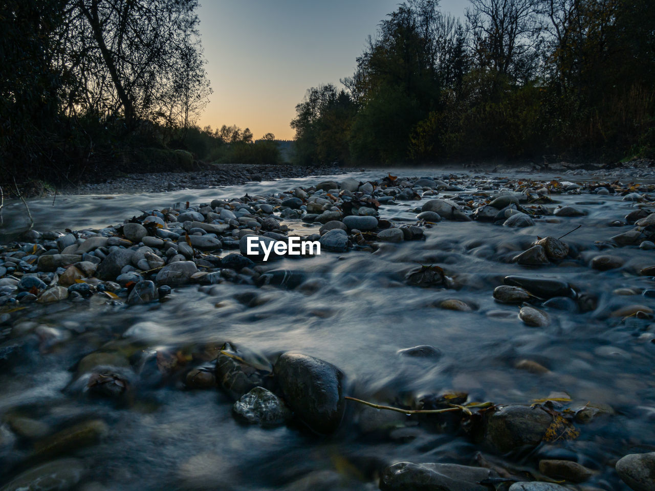 tree, water, rock, solid, no people, nature, plant, river, scenics - nature, non-urban scene, sky, rock - object, tranquility, beauty in nature, stone - object, tranquil scene, land, sunset, flowing water, surface level, outdoors, pebble, flowing, stream - flowing water