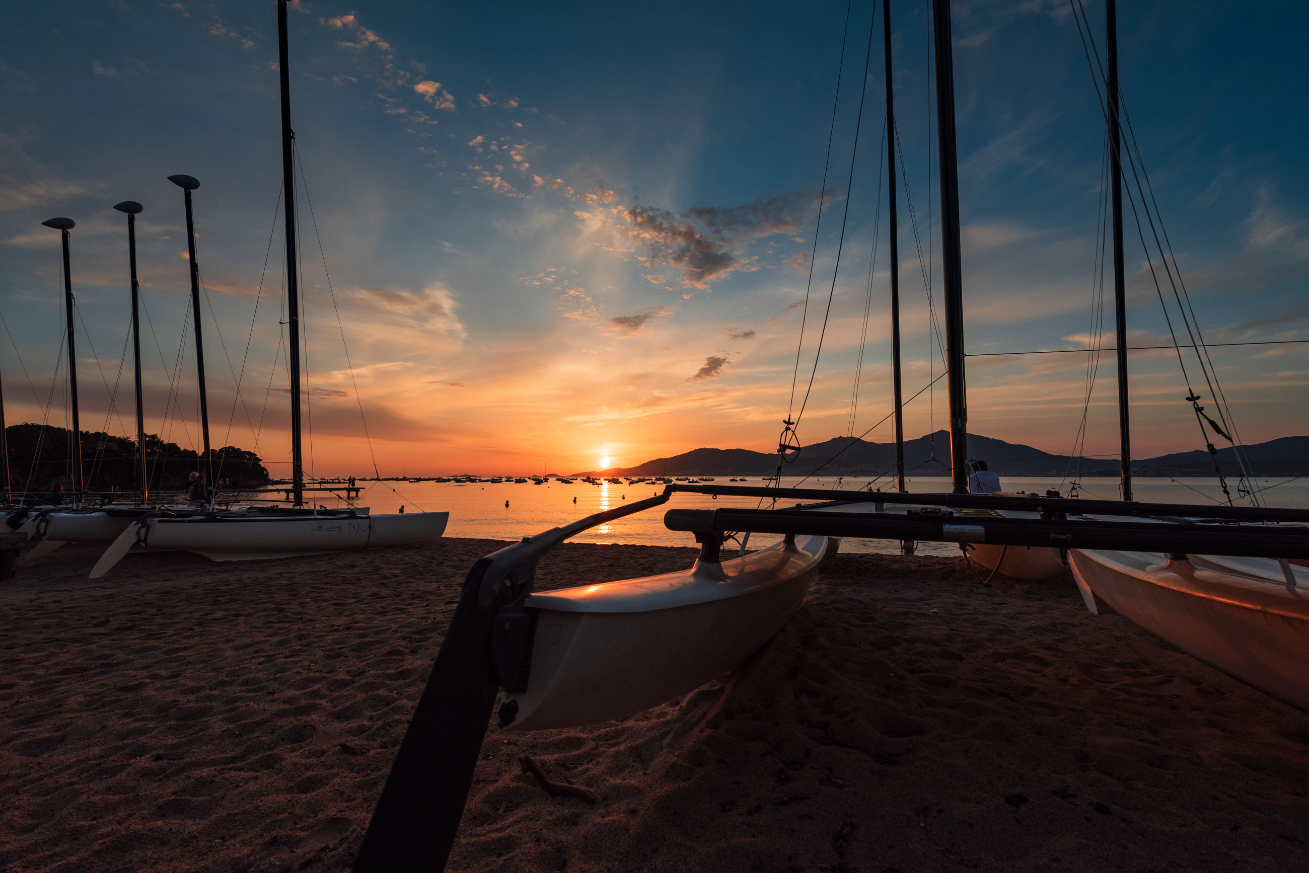 Sailboats moored on beach against sky during sunset