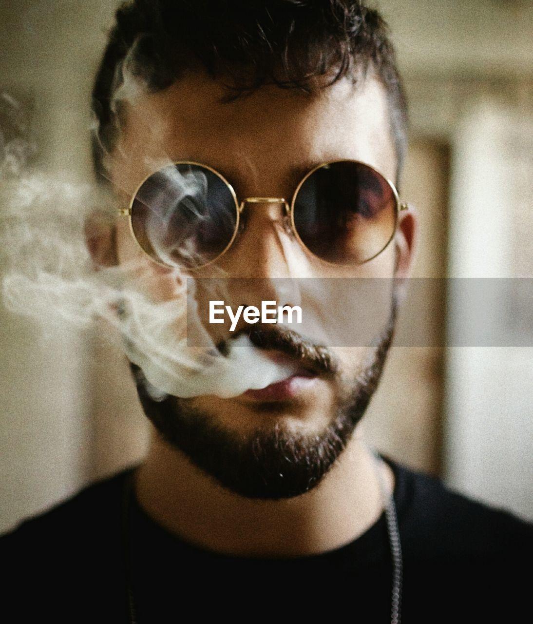Close-Up Portrait Of Young Man Smoking