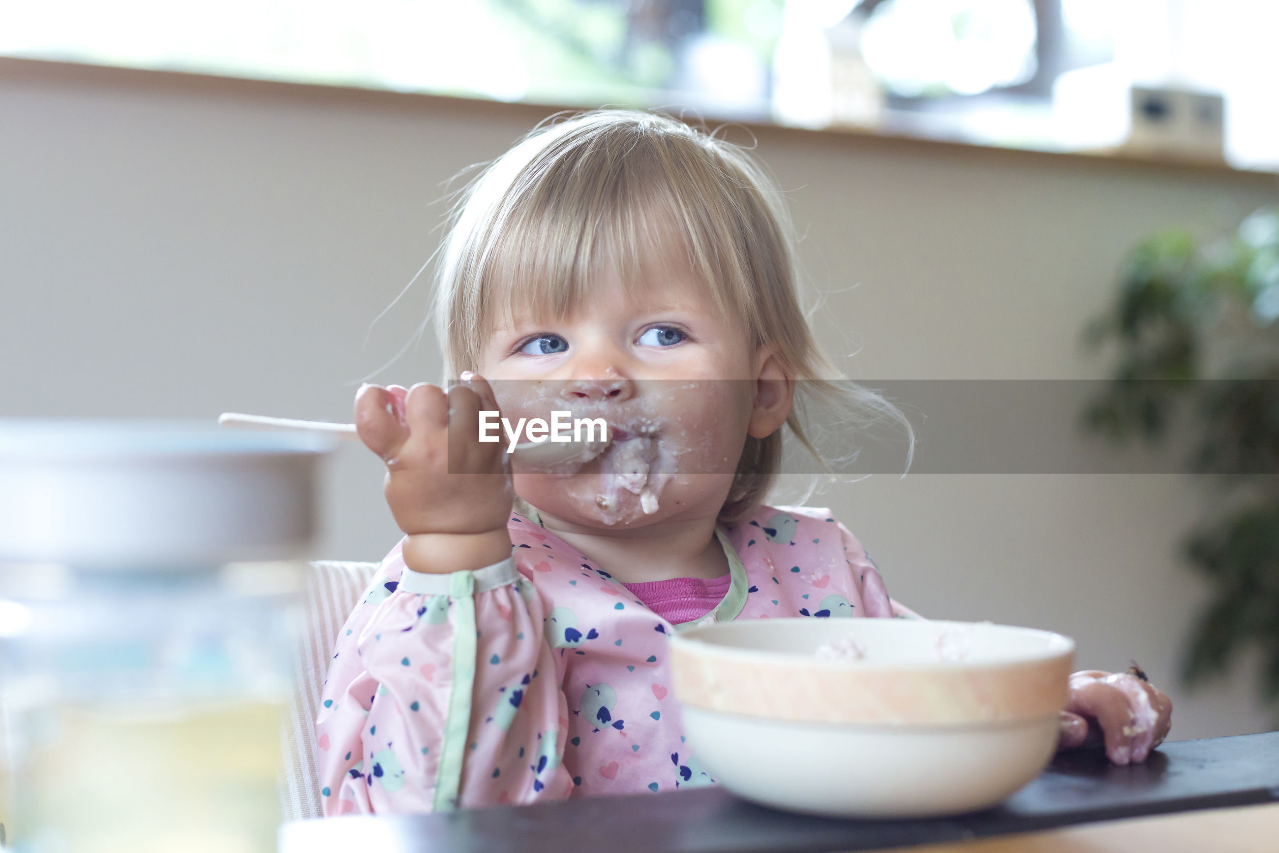 Cute girl eating ice cream at home