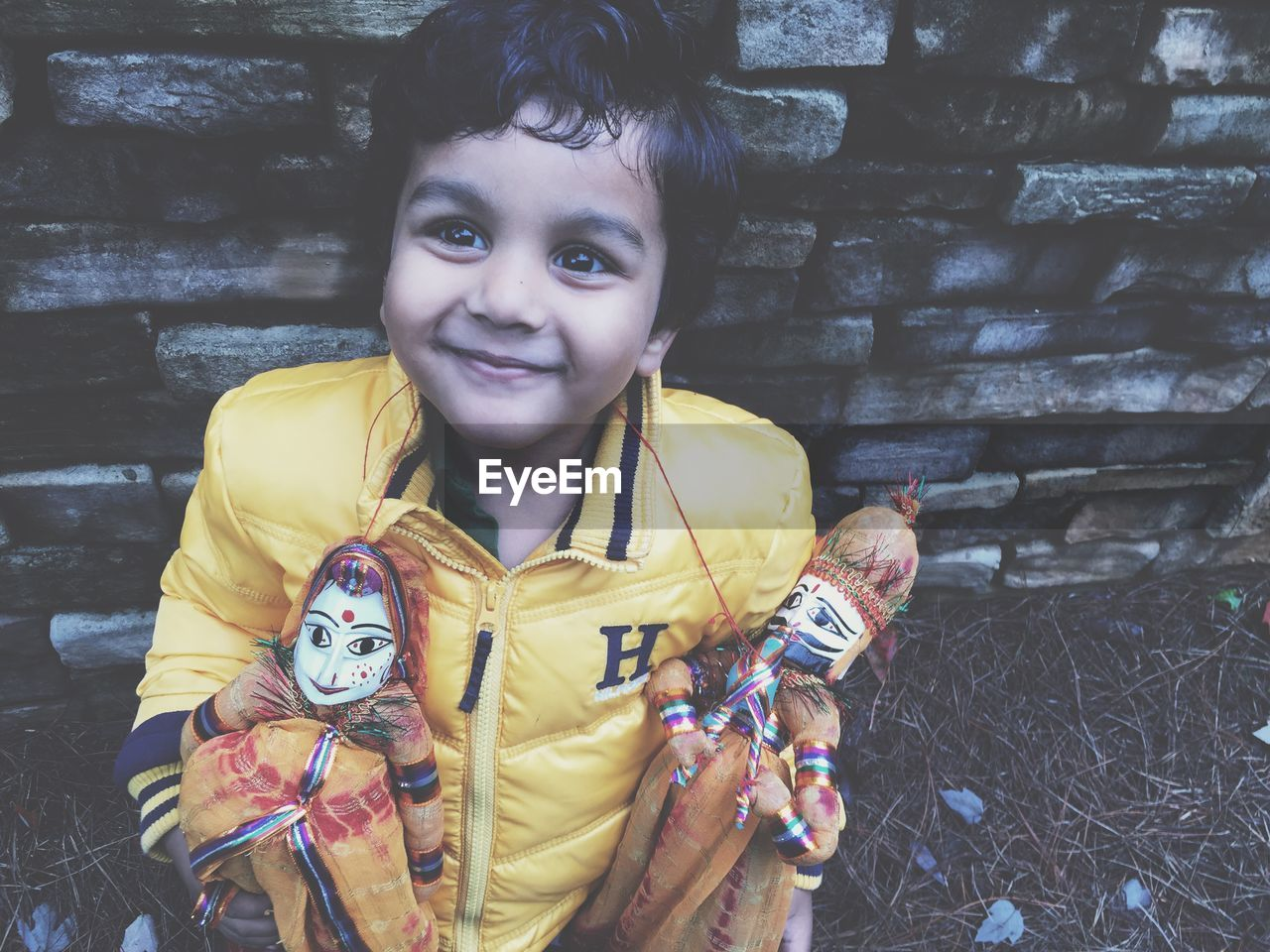 Boy holding puppets and standing against wall