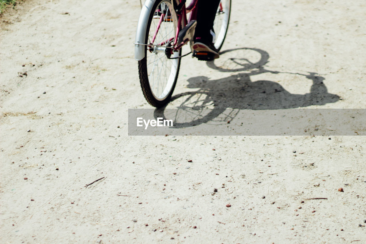 bicycle, transportation, mode of transport, day, outdoors, land vehicle, sunlight, shadow, low section, one person, real people, human body part, people