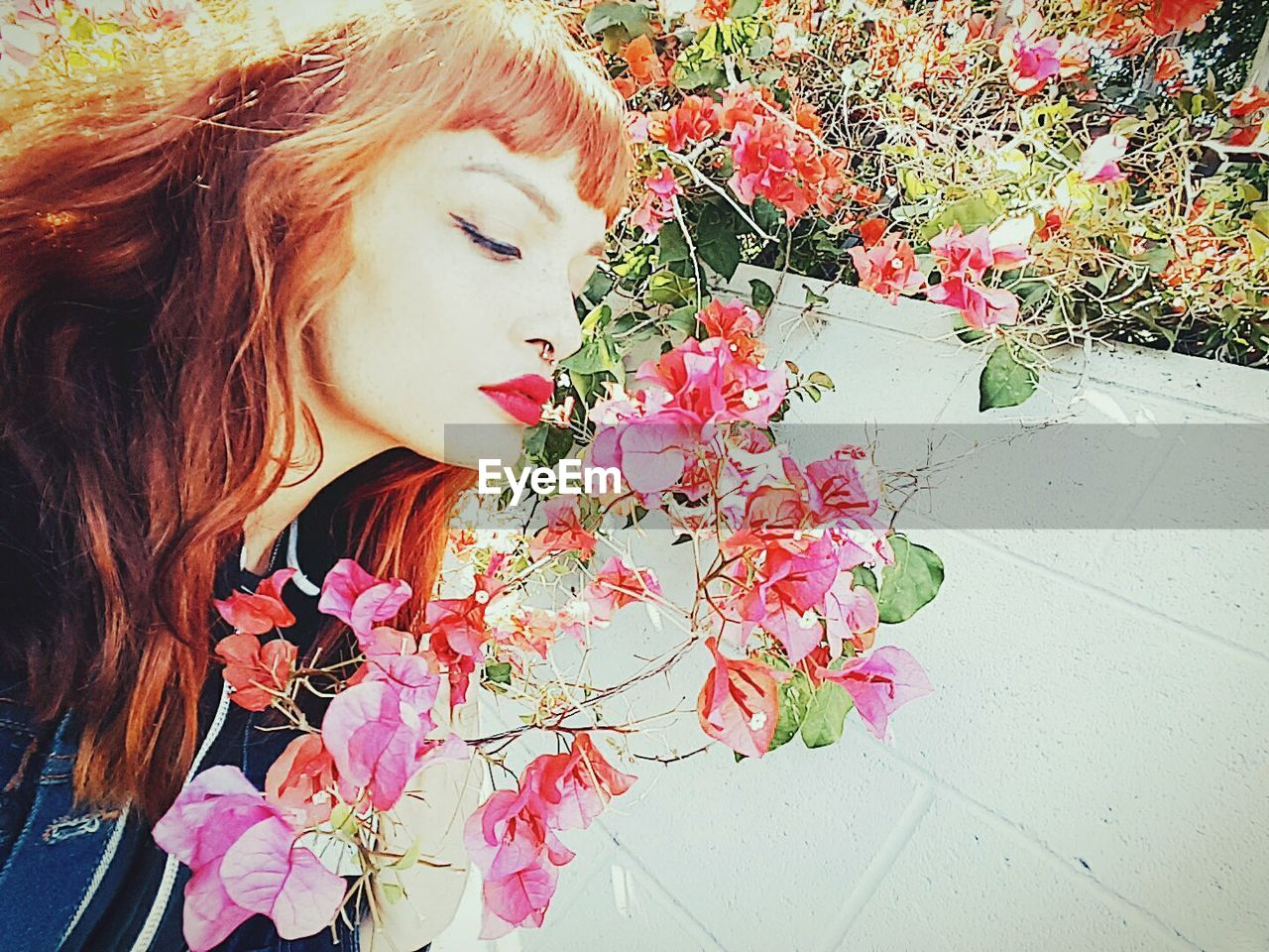Tilt shot of hipster woman looking at pink bougainvillea flowers against wall
