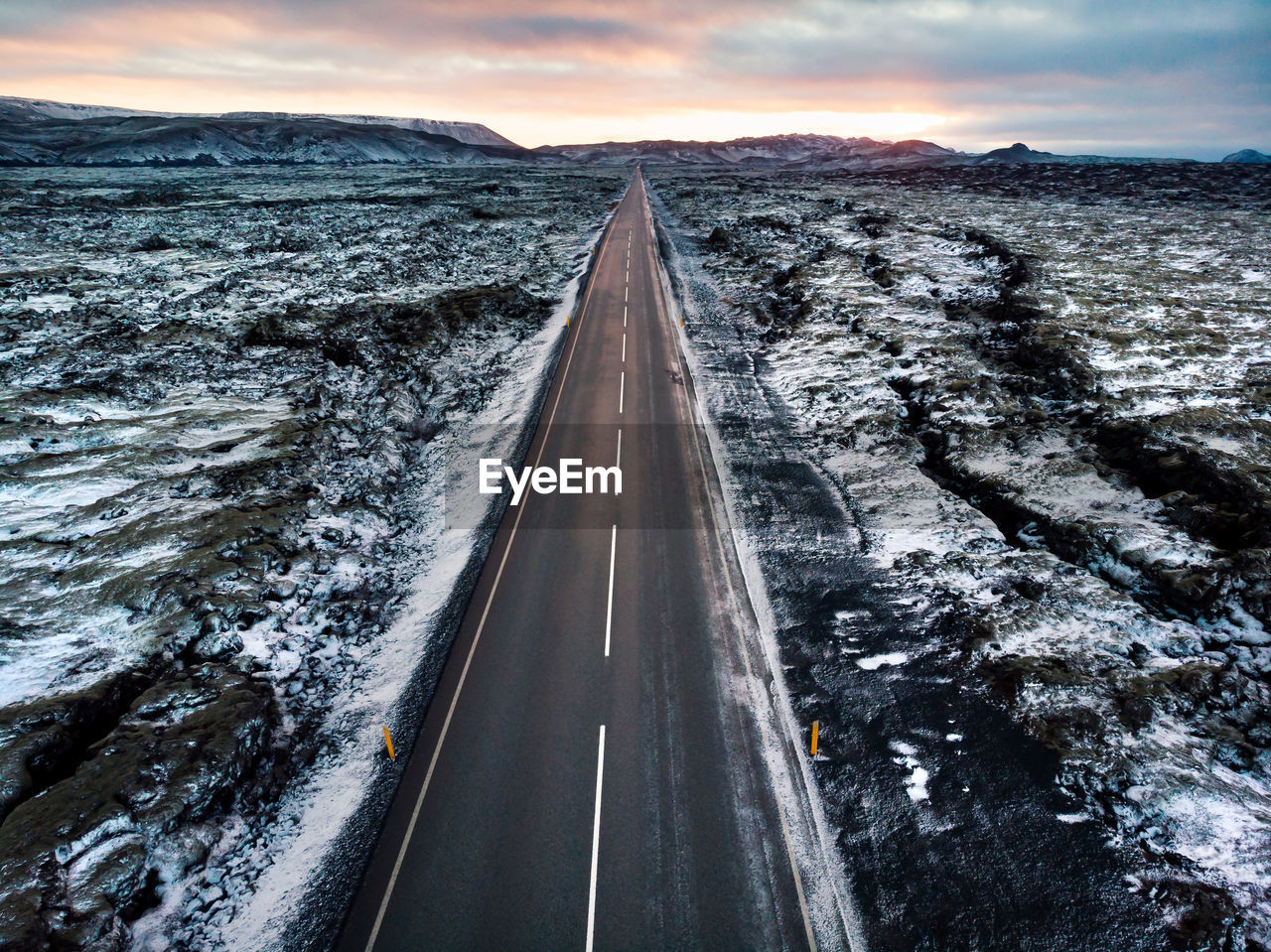 transportation, sky, the way forward, road, direction, nature, no people, diminishing perspective, snow, cold temperature, cloud - sky, winter, sign, vanishing point, beauty in nature, sunset, outdoors, symbol, scenics - nature, dividing line
