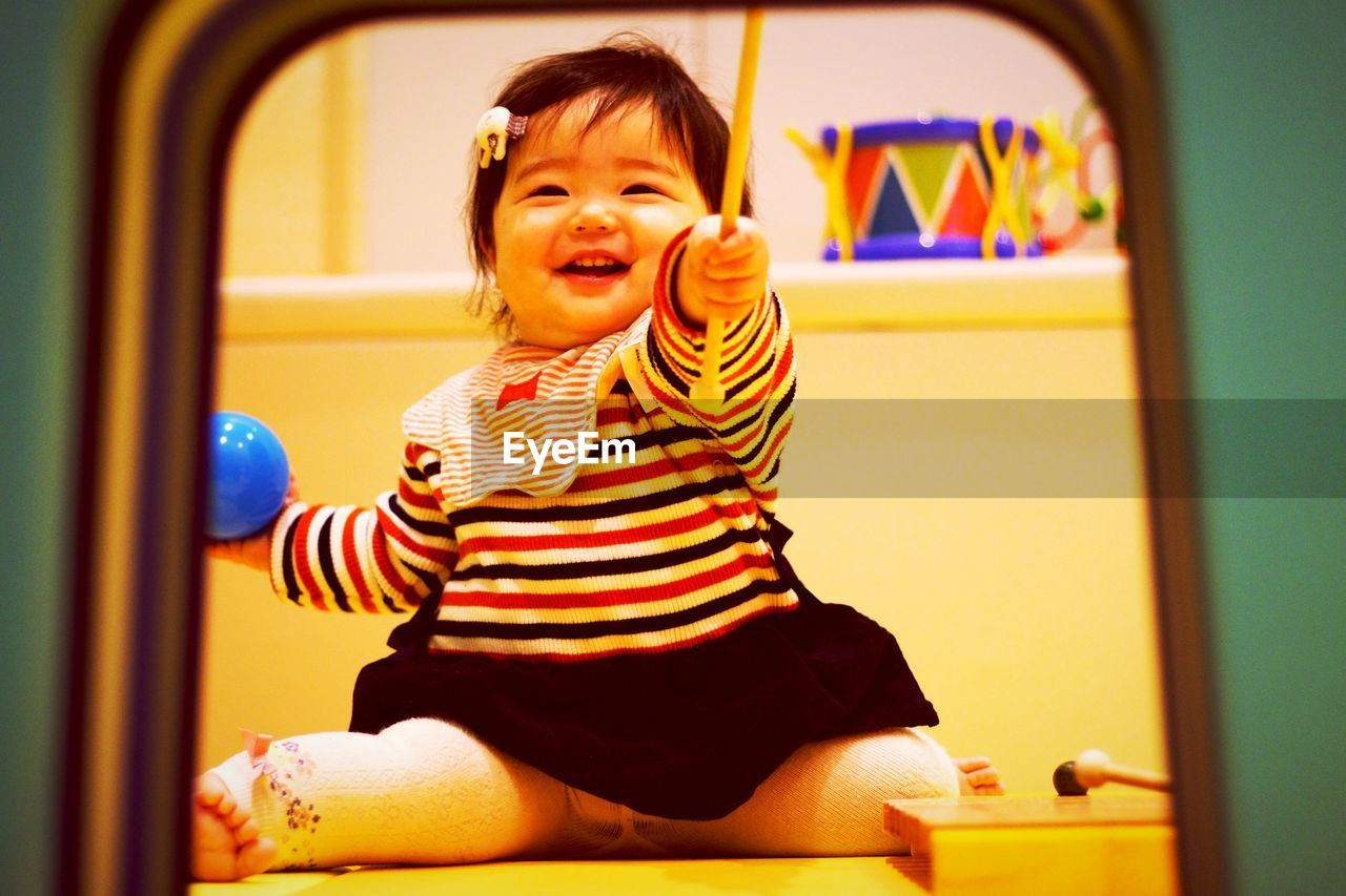 Cute smiling baby girl playing at home