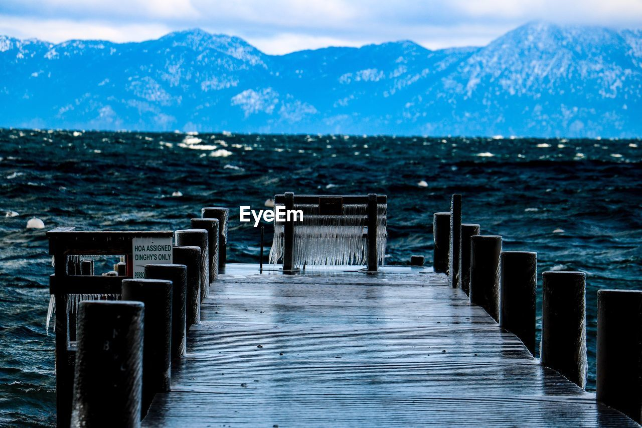 Wooden Pier On Sea By Mountains Against Sky