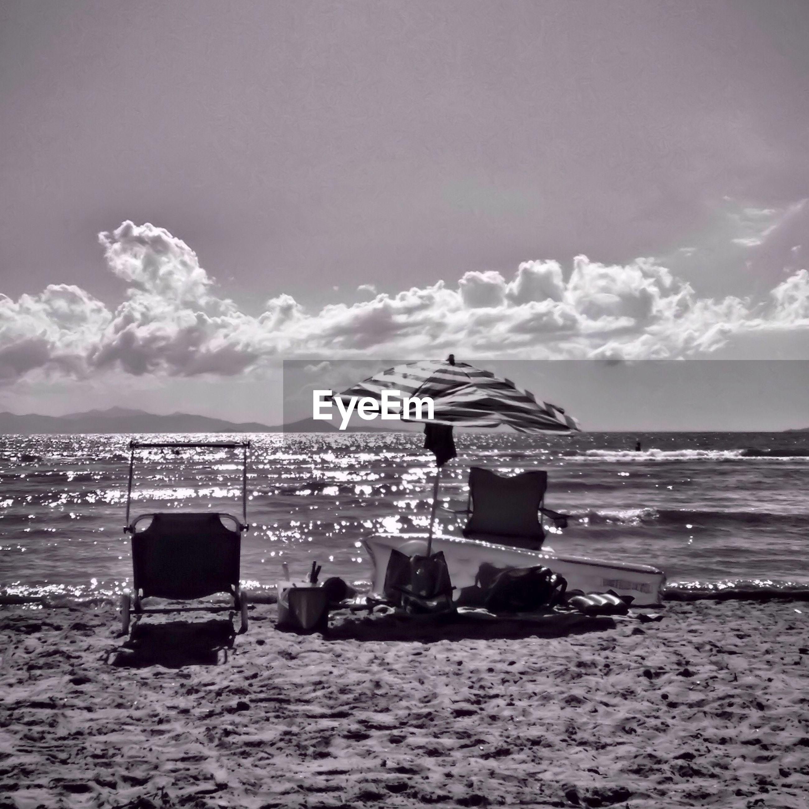 Chair and parasol on beach against sky