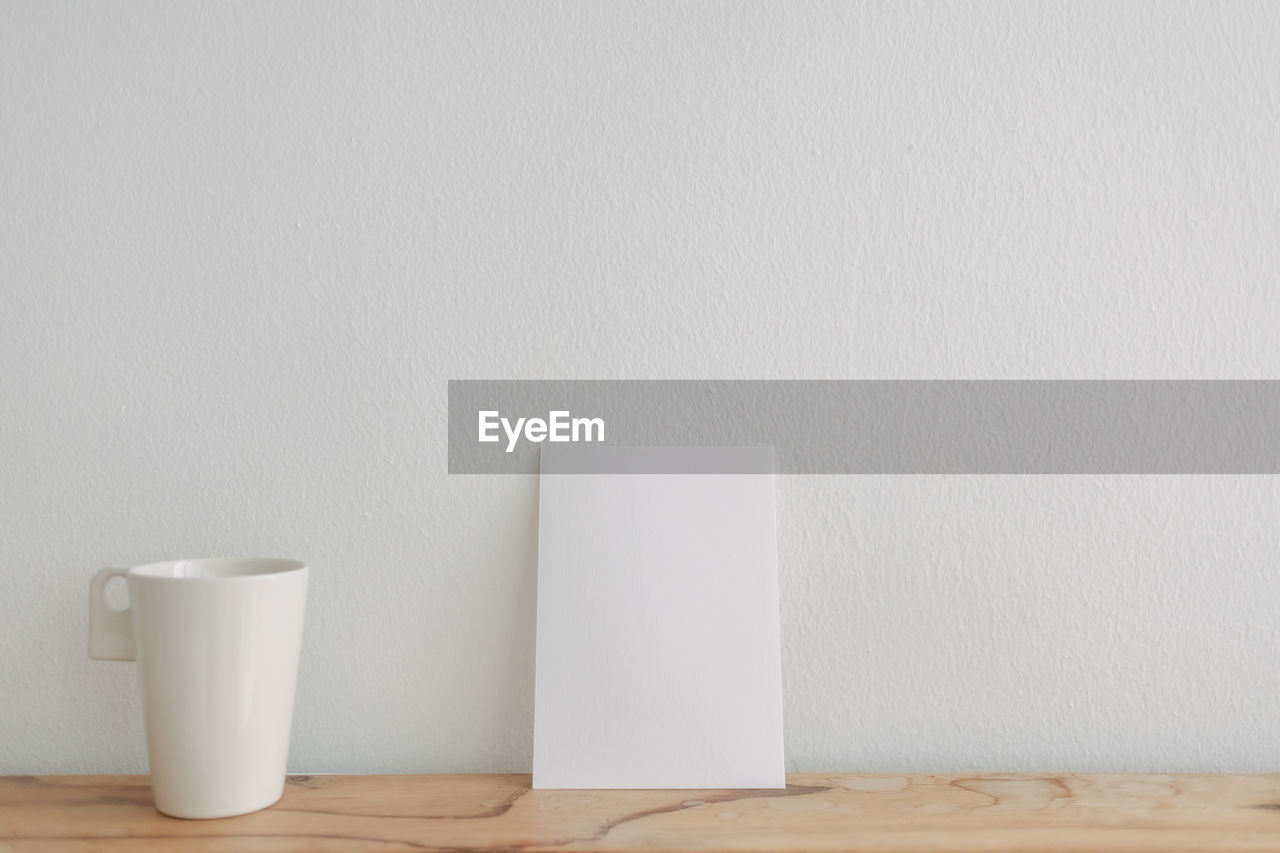 CLOSE-UP OF COFFEE CUP ON WHITE TABLE AGAINST WALL AT HOME