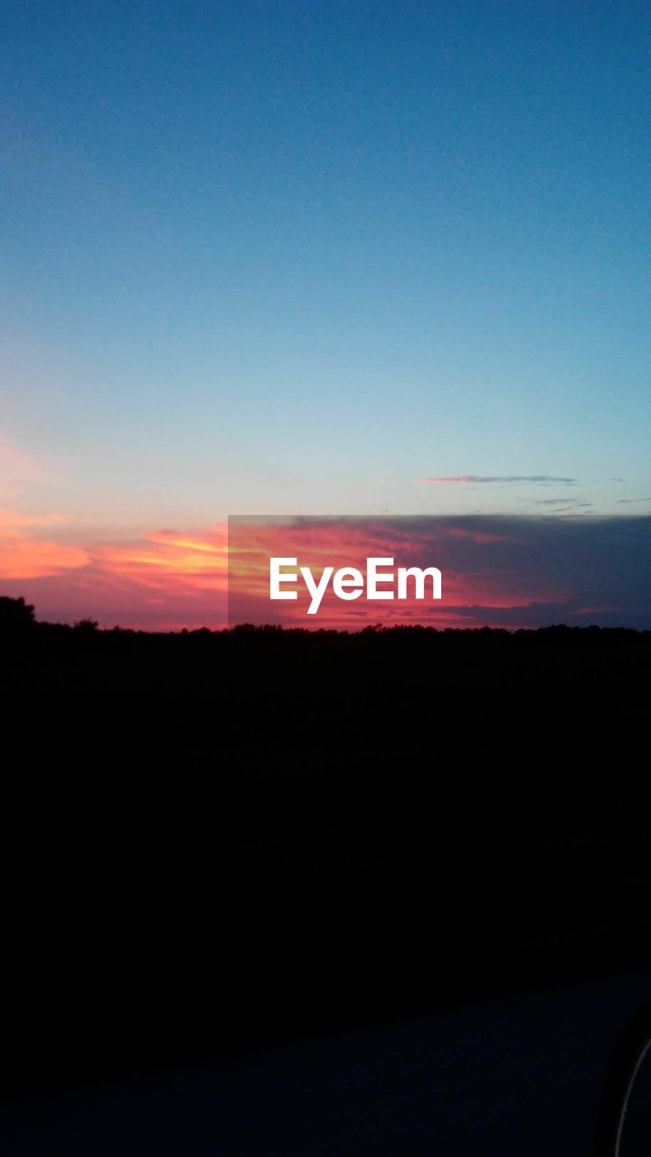 sky, sunset, copy space, silhouette, scenics - nature, beauty in nature, tranquility, tranquil scene, nature, orange color, no people, environment, landscape, idyllic, clear sky, outdoors, blue, non-urban scene, horizon