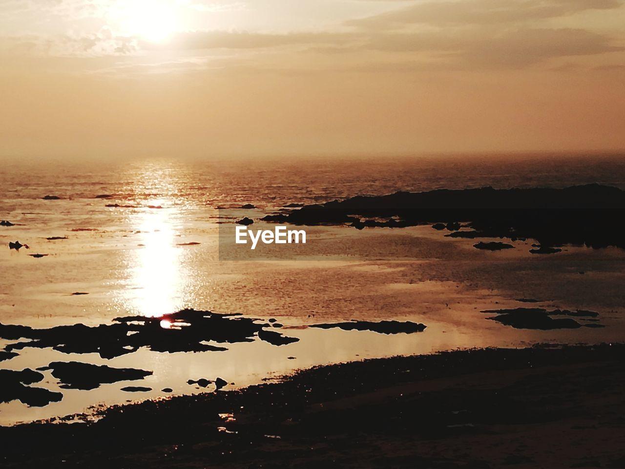 water, sky, sunset, scenics - nature, tranquility, beauty in nature, tranquil scene, sea, reflection, nature, beach, cloud - sky, land, sunlight, no people, idyllic, sun, orange color, non-urban scene, outdoors