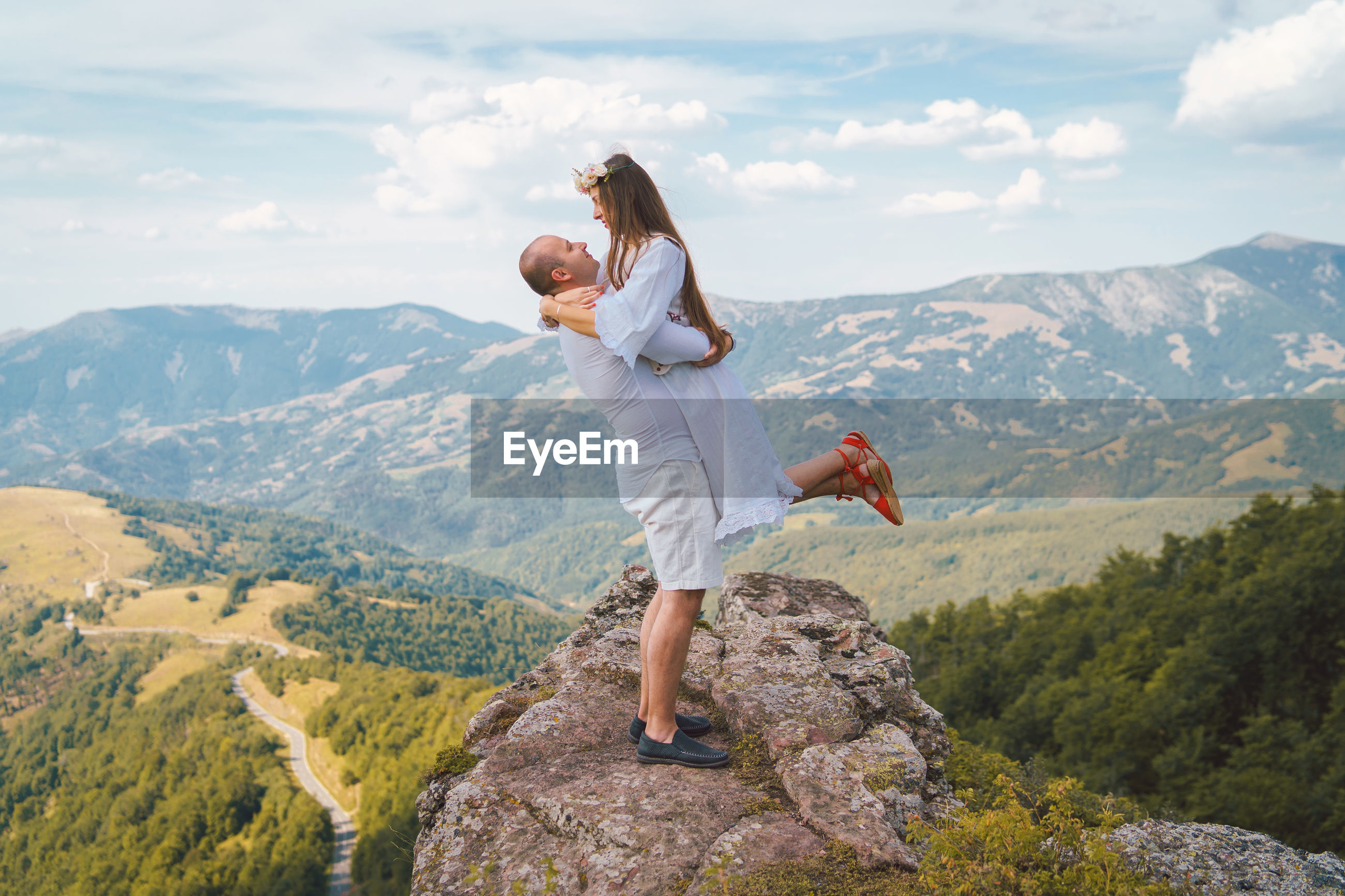 Man carrying woman while standing on mountain