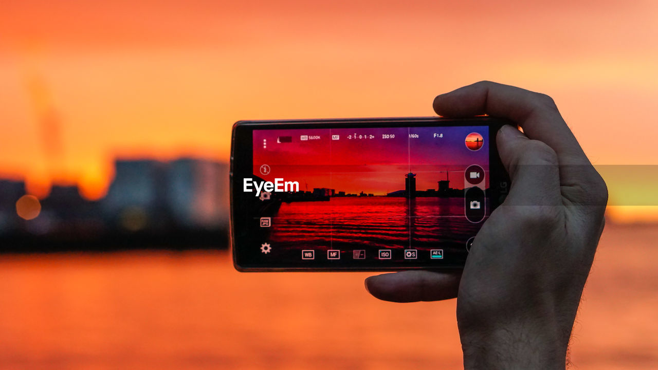 Cropped image of man photographing river through mobile phone during sunset