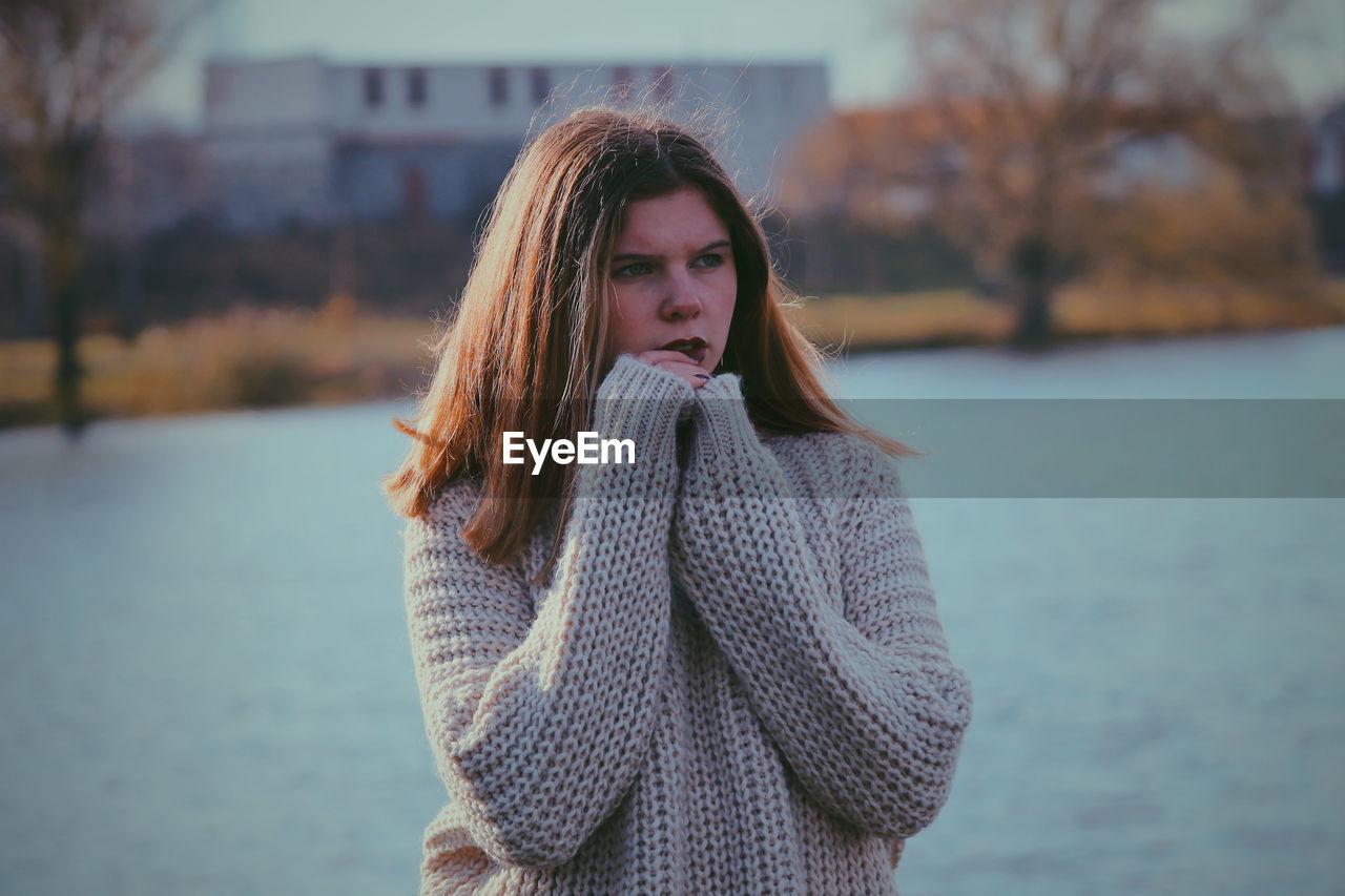 Teenage girl standing against river