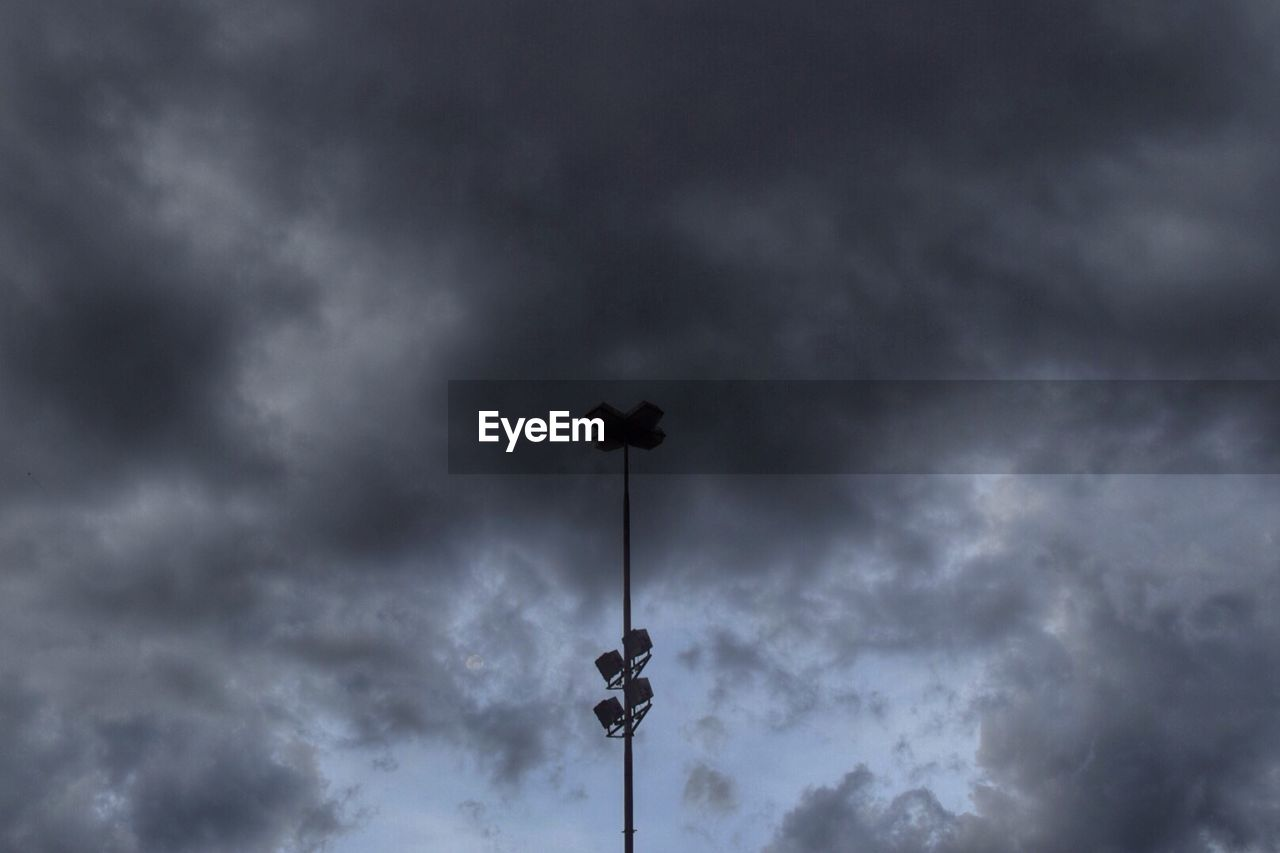 Low angle view of floodlight against cloudy sky at dusk