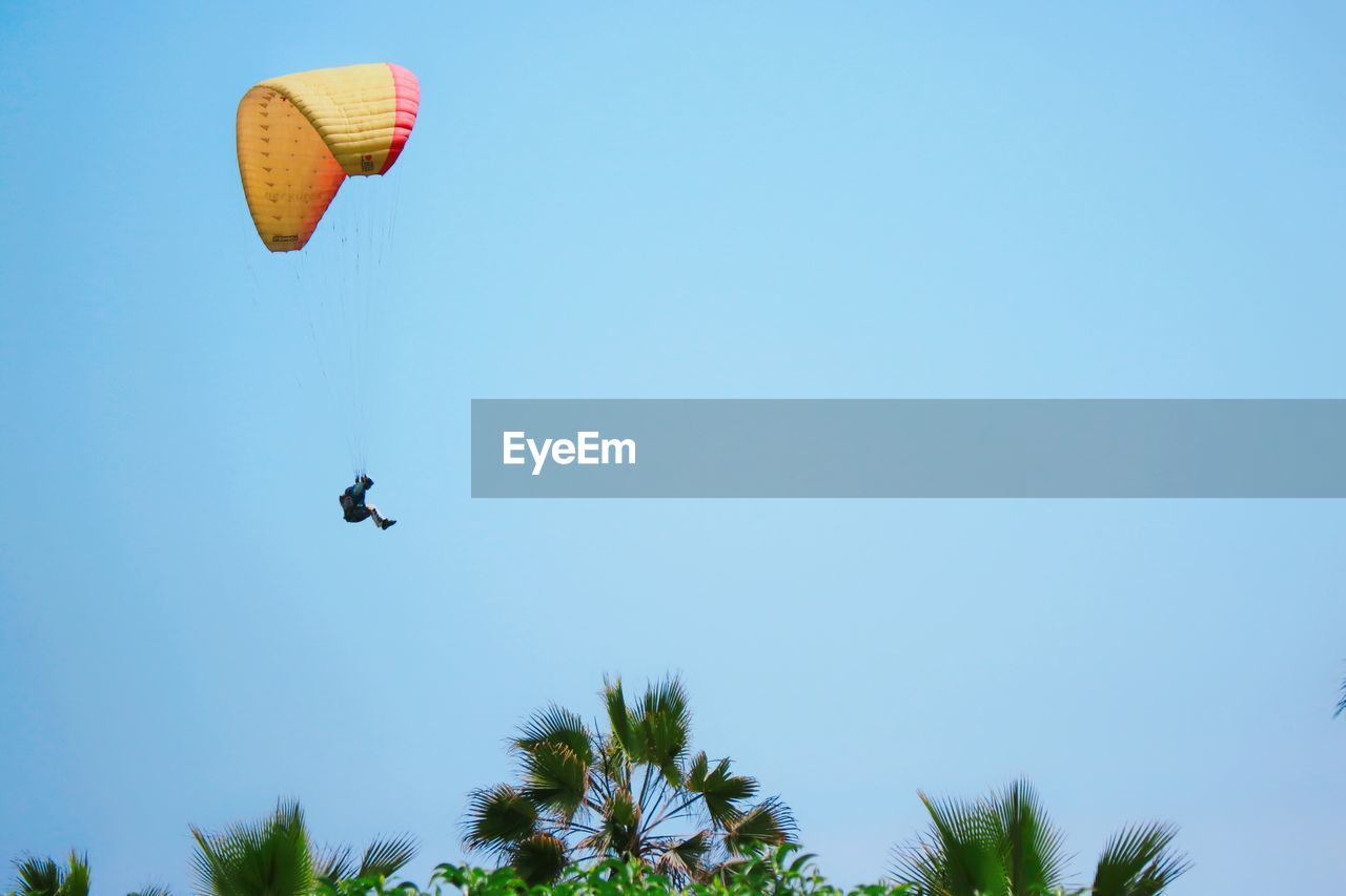 mid-air, sky, flying, sport, low angle view, extreme sports, adventure, clear sky, leisure activity, parachute, paragliding, copy space, unrecognizable person, day, nature, motion, blue, transportation, real people, tree, freedom