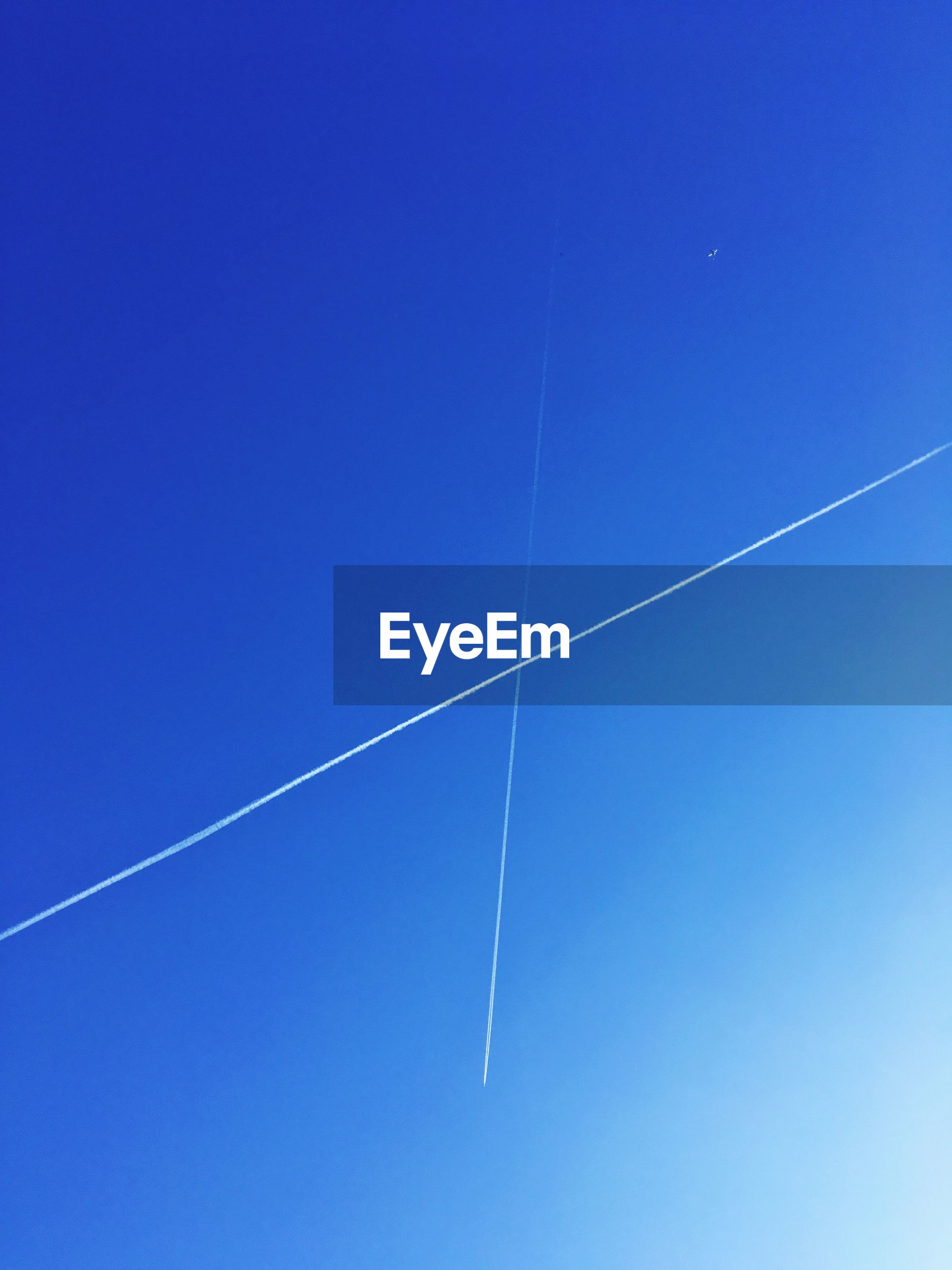 Low angle view of vapor trails in clear blue sky