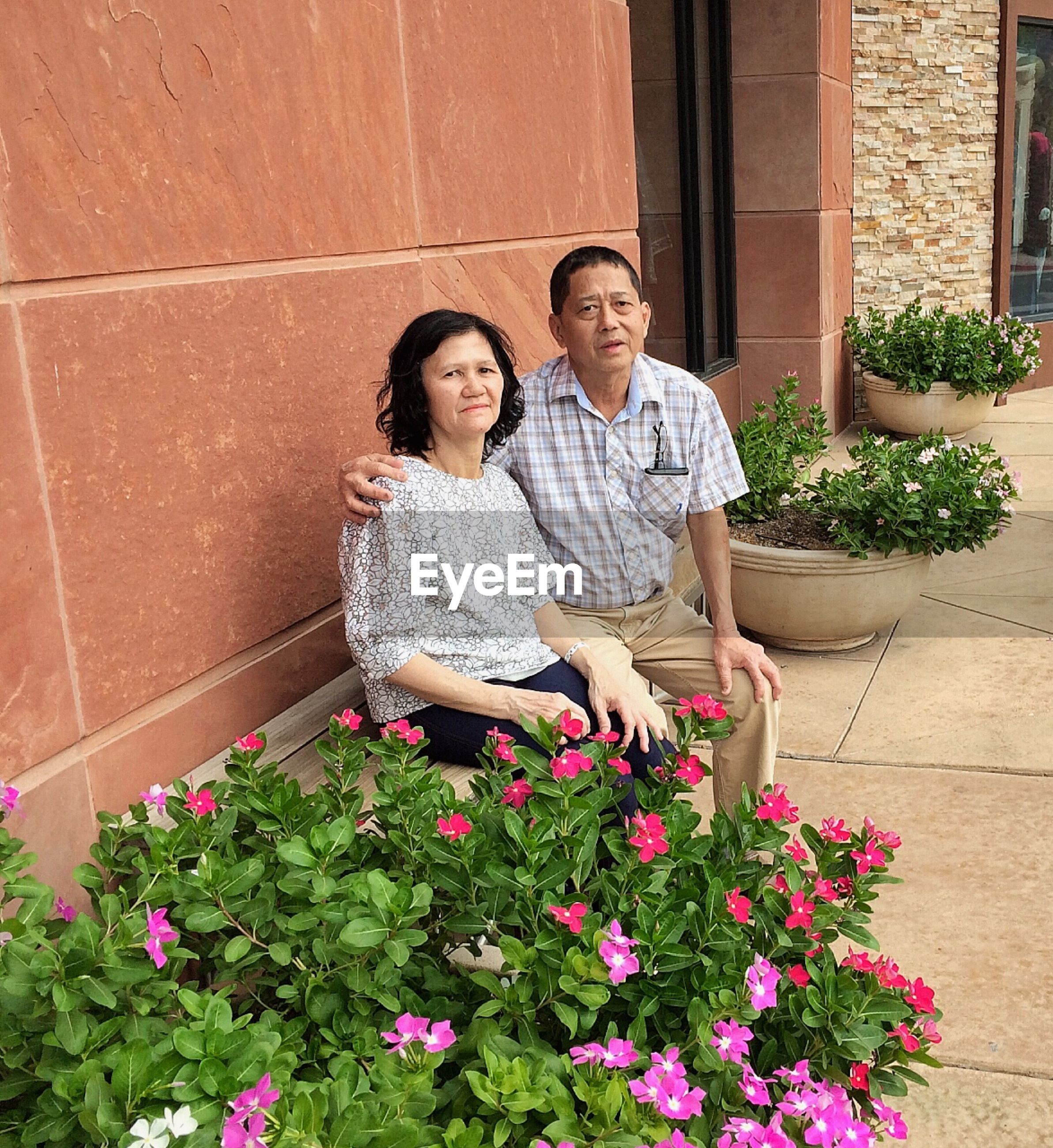 Portrait of senior couple sitting by flowers