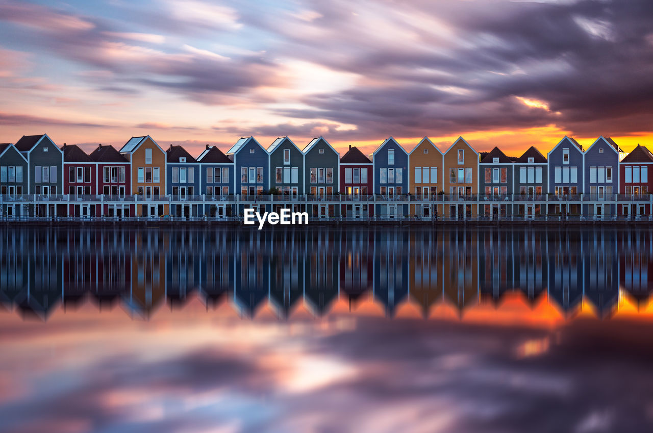 Reflection Of Colorful Houses On Calm Sea Against Cloudy Sky At Sunset