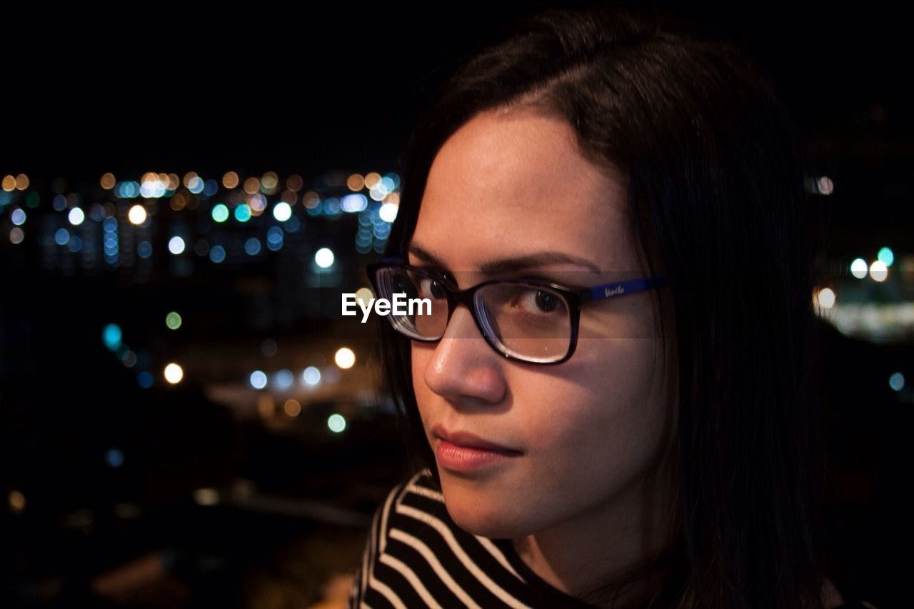 night, young adult, illuminated, eyeglasses, focus on foreground, one person, headshot, glasses, young women, beauty, beautiful woman, close-up, portrait, outdoors, adult, people, adults only