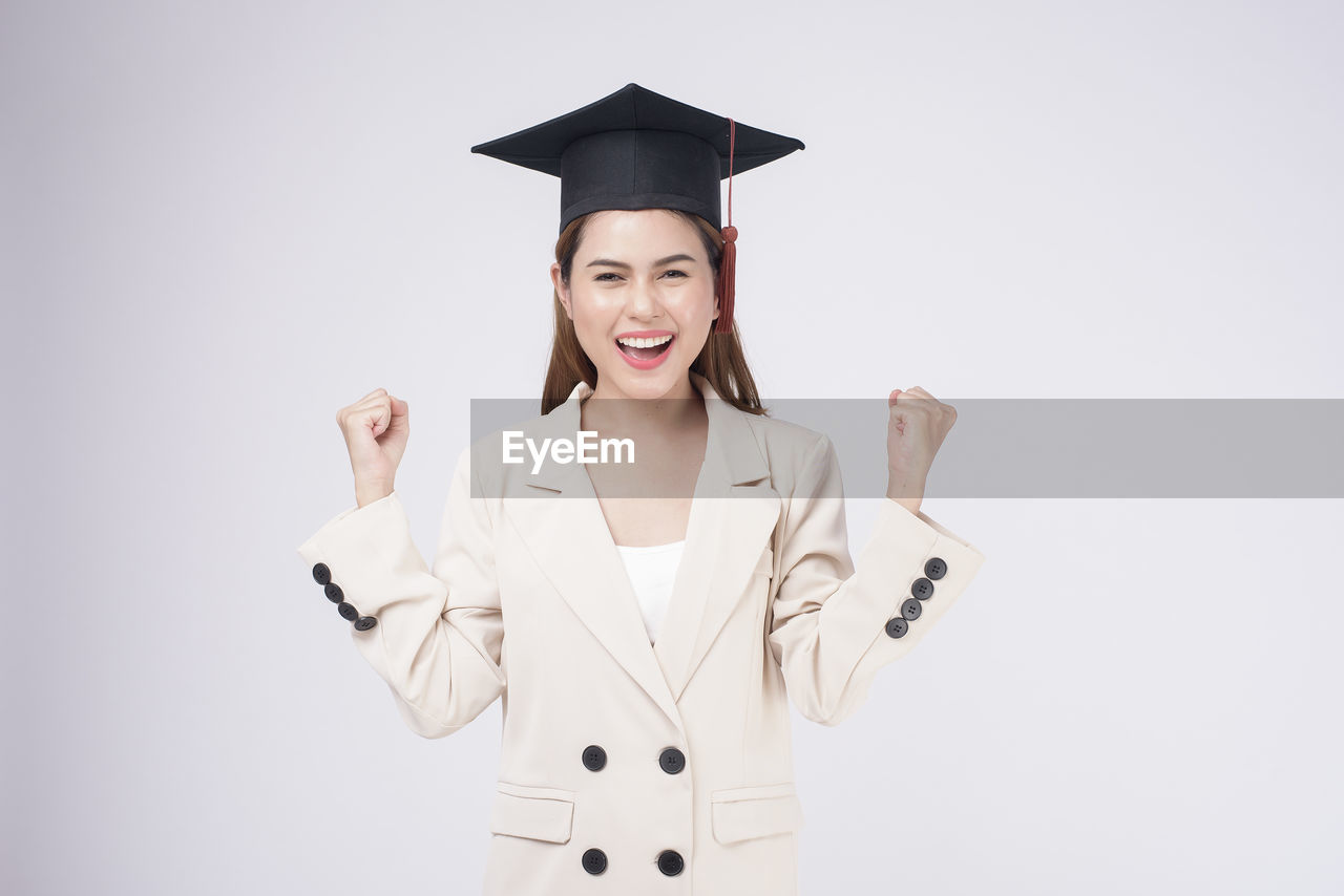SMILING YOUNG WOMAN HOLDING CAMERA OVER WHITE BACKGROUND