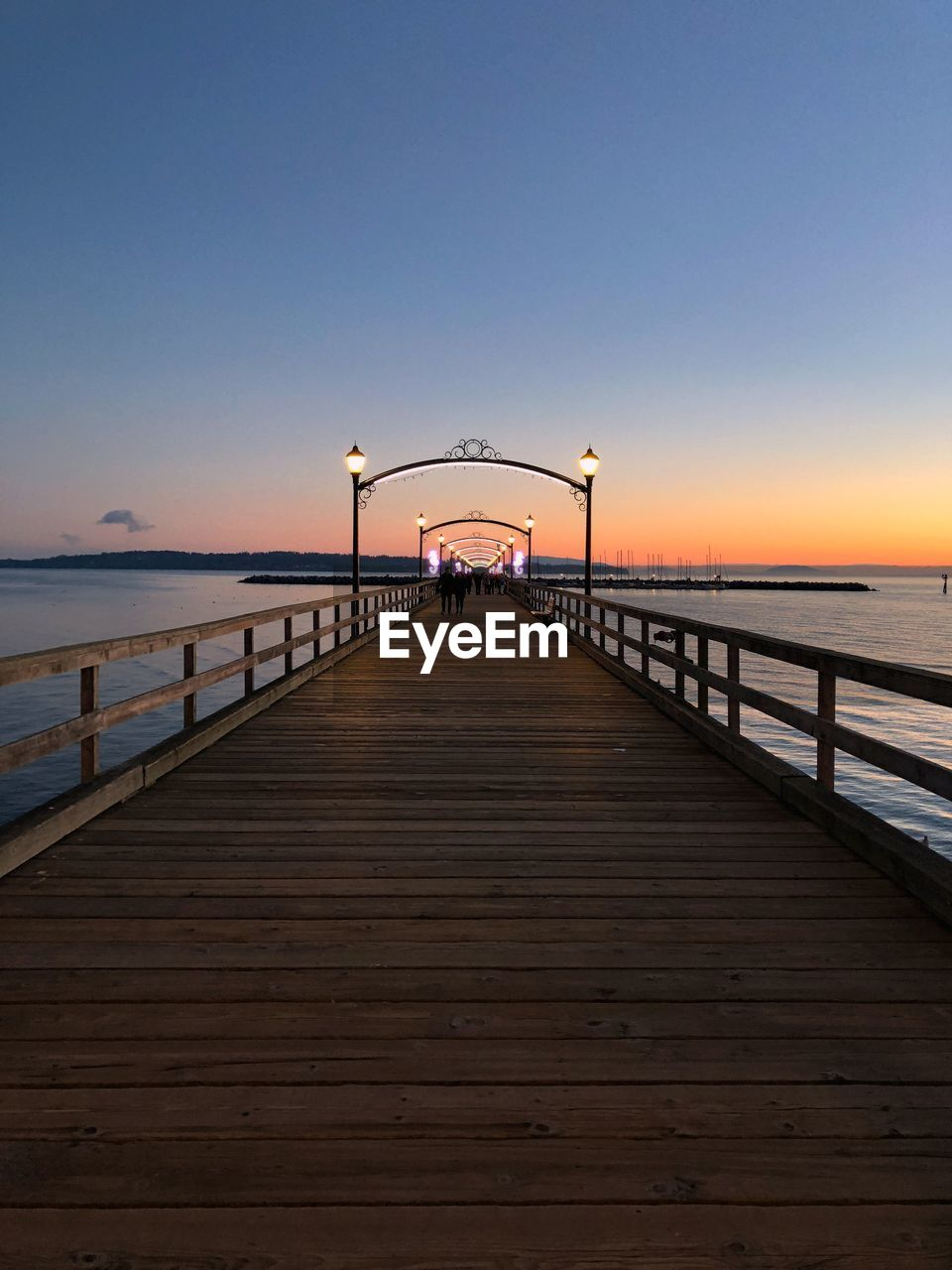 sky, water, sea, pier, horizon over water, horizon, the way forward, scenics - nature, sunset, railing, beauty in nature, direction, nature, tranquility, clear sky, real people, copy space, diminishing perspective, tranquil scene, outdoors, long, wood paneling