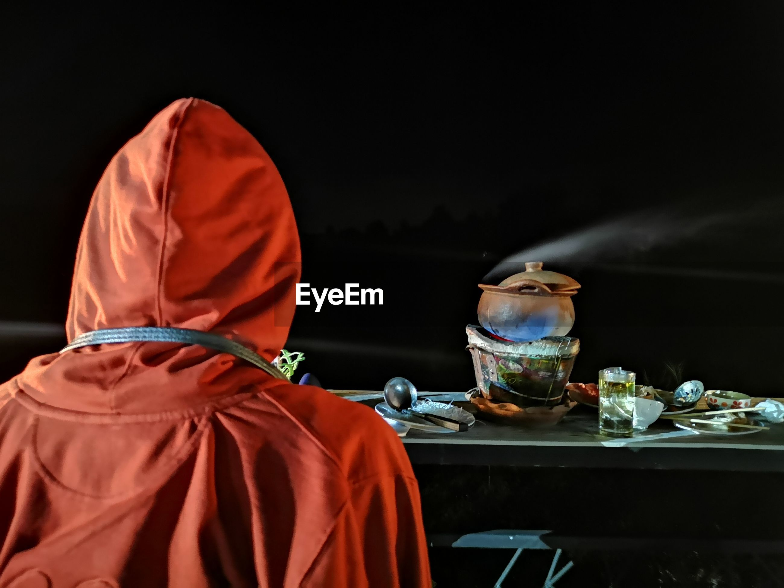 Rear view of person standing by food in table