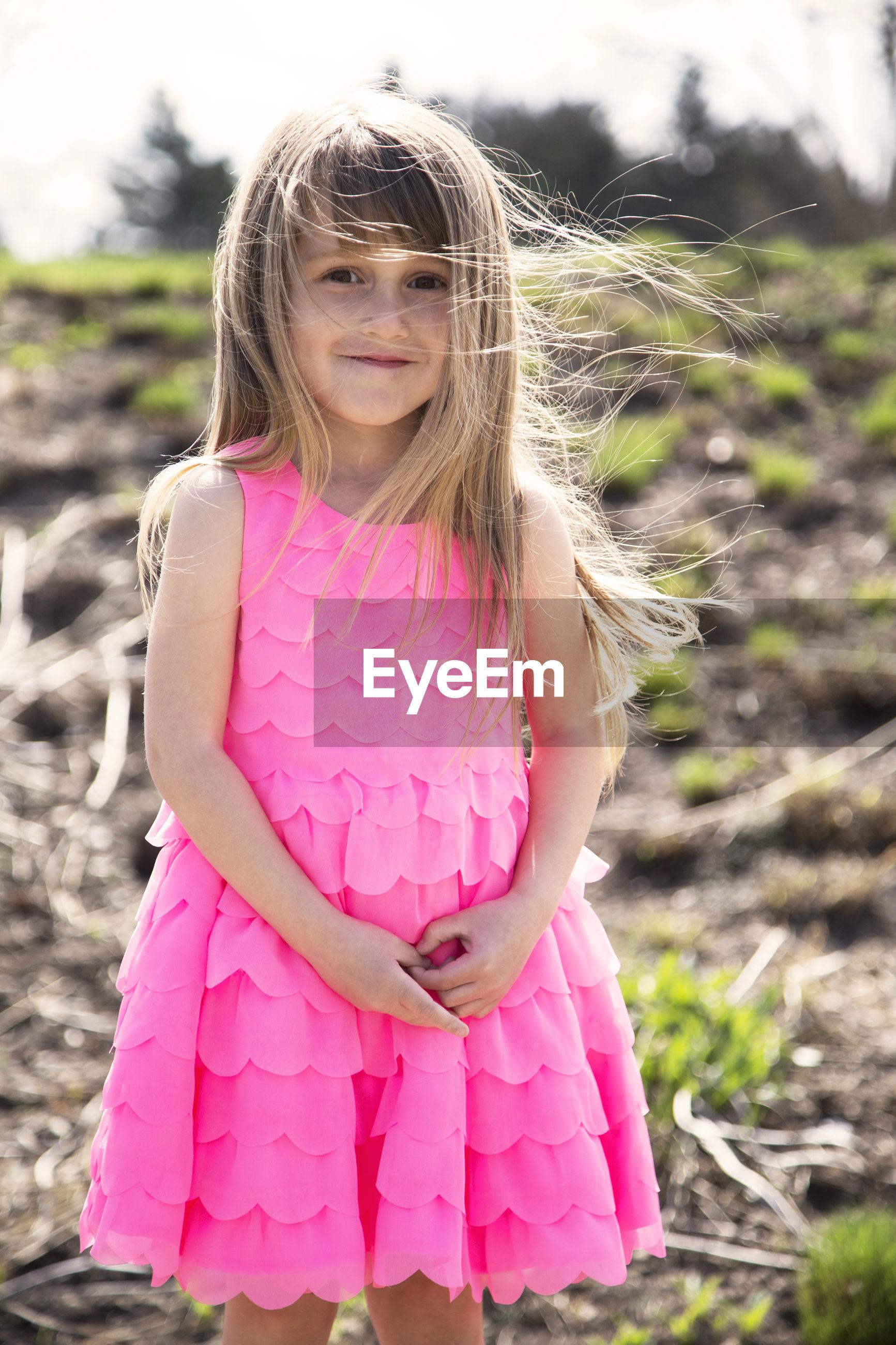 Portrait of girl standing on field