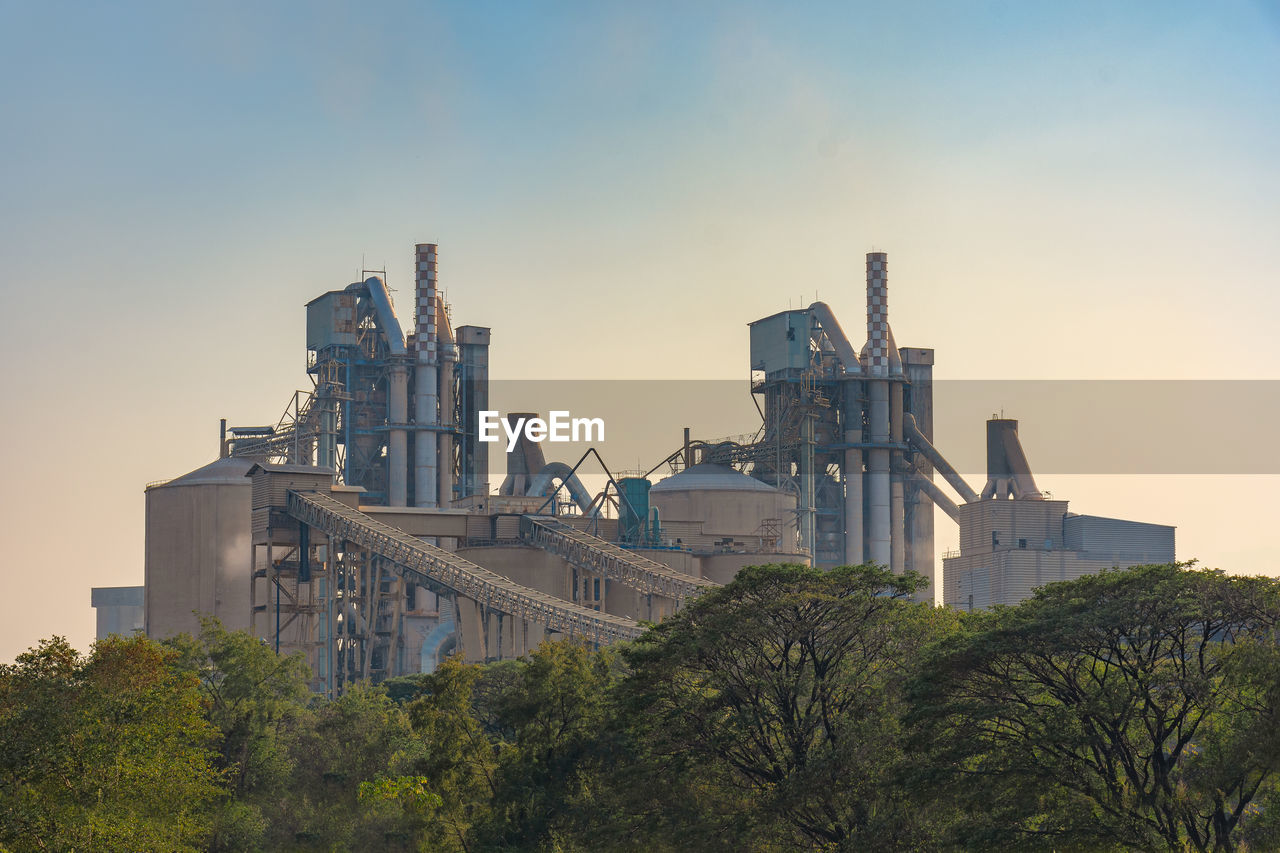 LOW ANGLE VIEW OF FACTORY AGAINST SKY DURING SUNSET