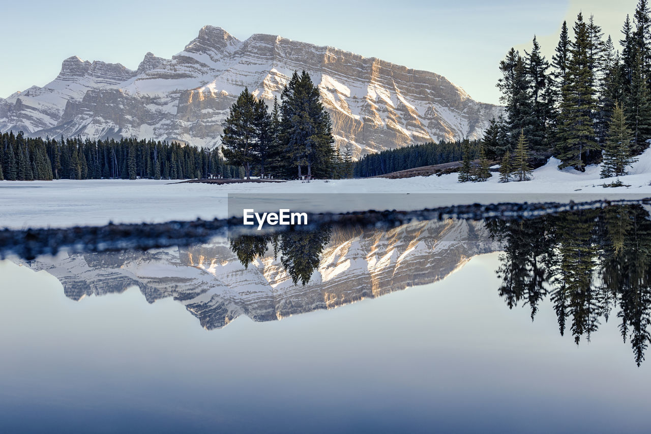 Scenic View Of Lake With Snowcapped Mountains Reflection Against Sky