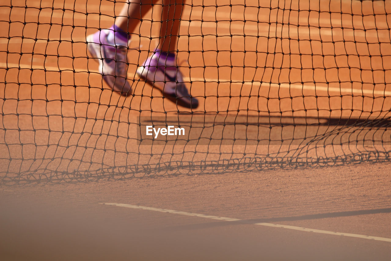 Low Section Of Person Seen Through Net At Tennis Court