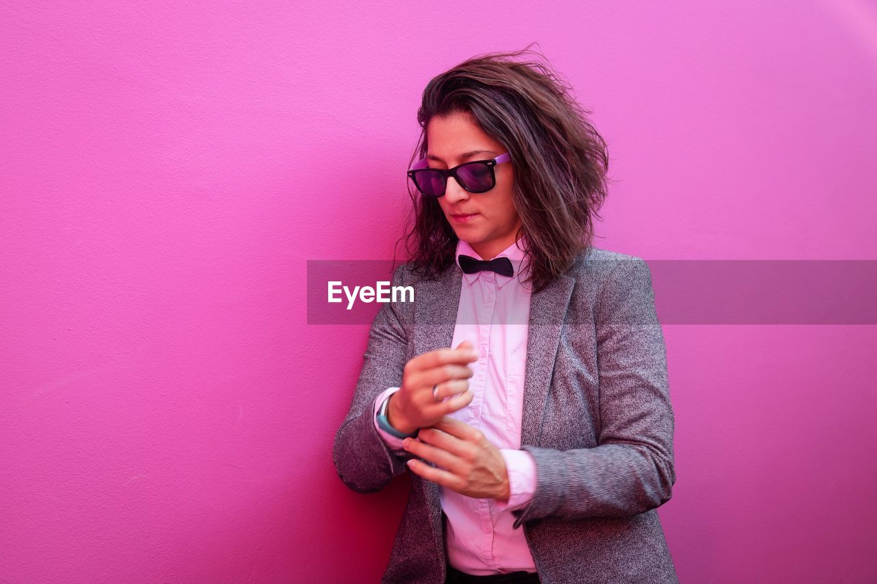 pink color, glasses, one person, front view, fashion, young adult, standing, sunglasses, pink background, indoors, lifestyles, young women, real people, waist up, clothing, casual clothing, wall - building feature, colored background, hairstyle, beautiful woman, purple
