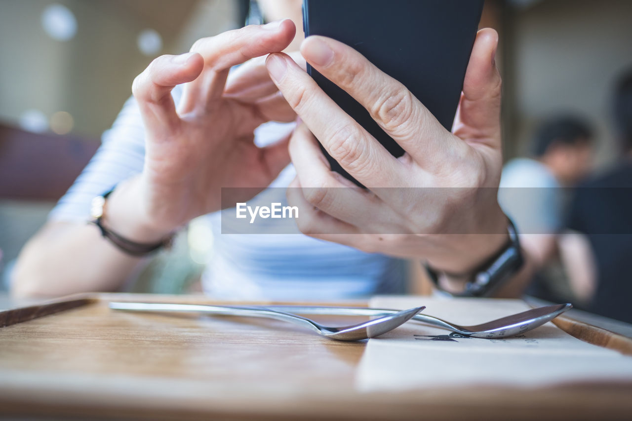 Midsection of person using mobile phone at table