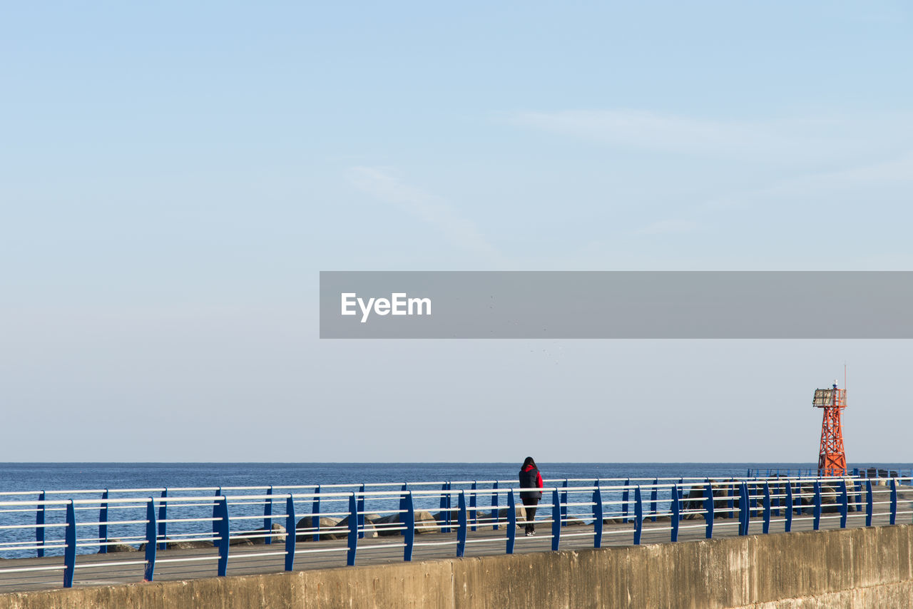 water, sea, sky, horizon over water, horizon, scenics - nature, beach, beauty in nature, nature, real people, day, land, tranquility, tranquil scene, railing, rear view, built structure, lifestyles, men, outdoors
