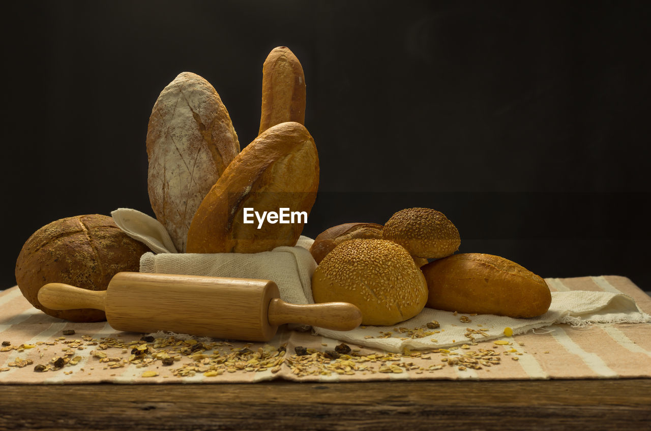Close-Up Of Bread And Rolling Pin On Table Against Black Background