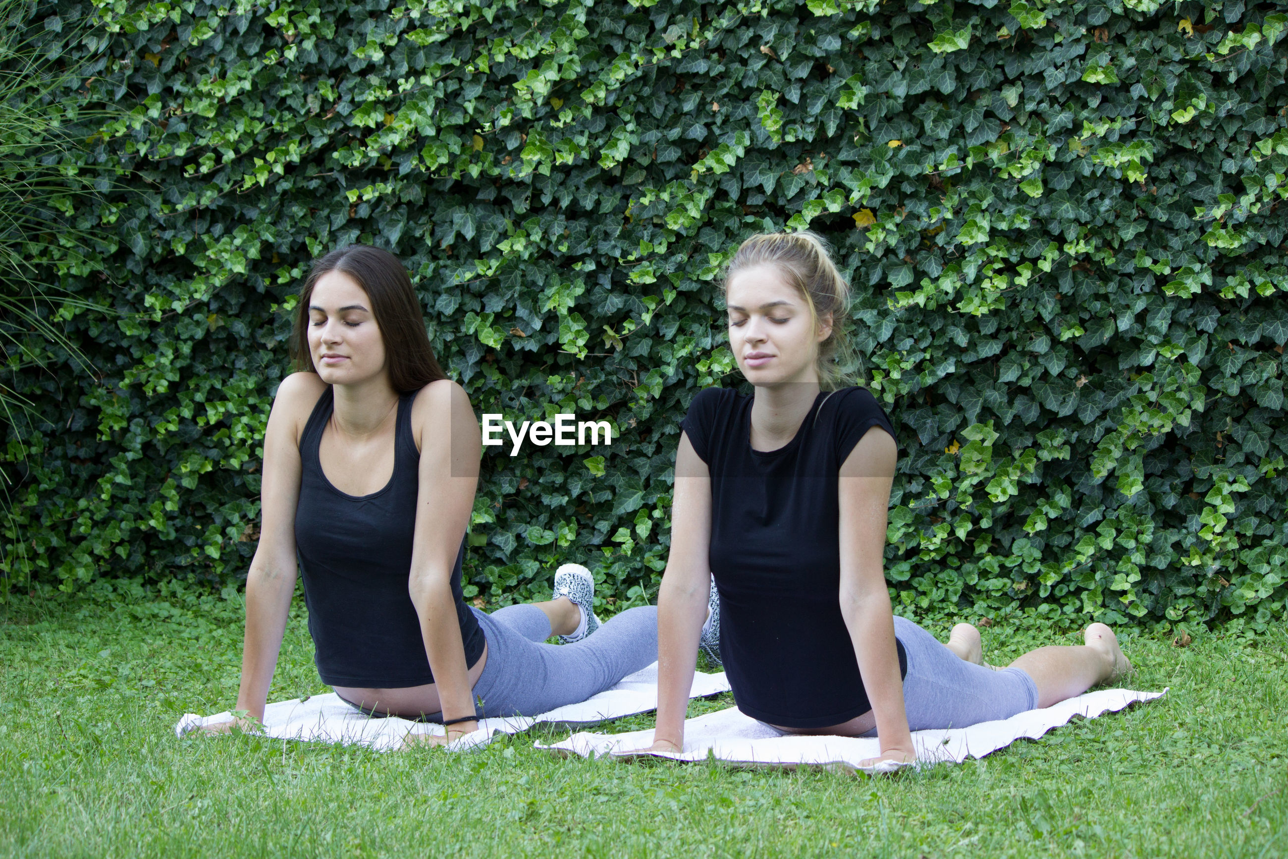 Women with eyes closed exercising against plants in park