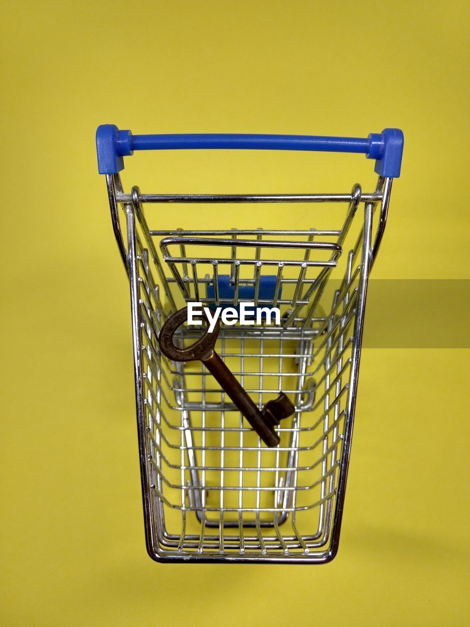 Close-up of shopping cart and key on yellow background