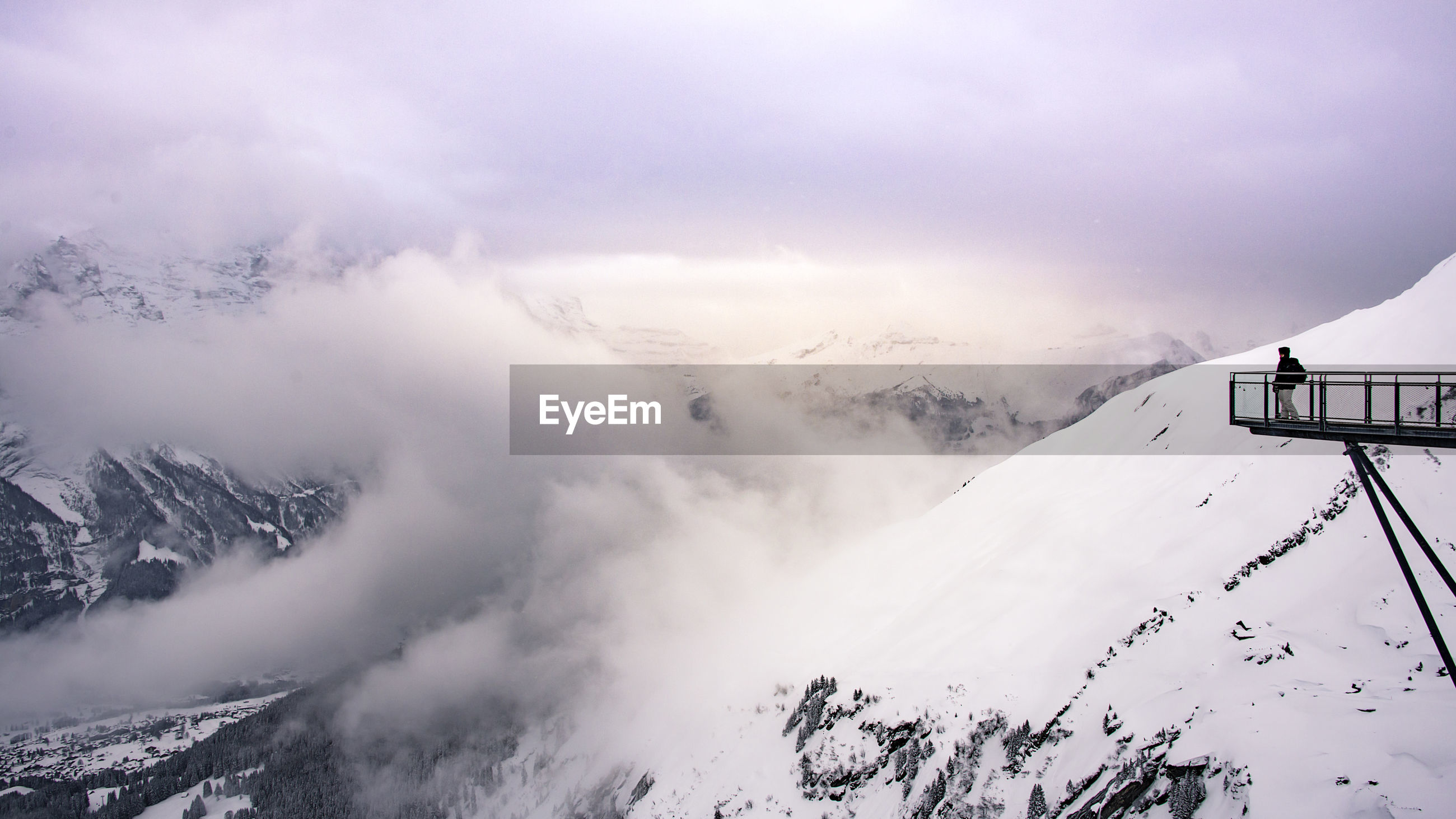 Man looking at snow covered mountains against sky