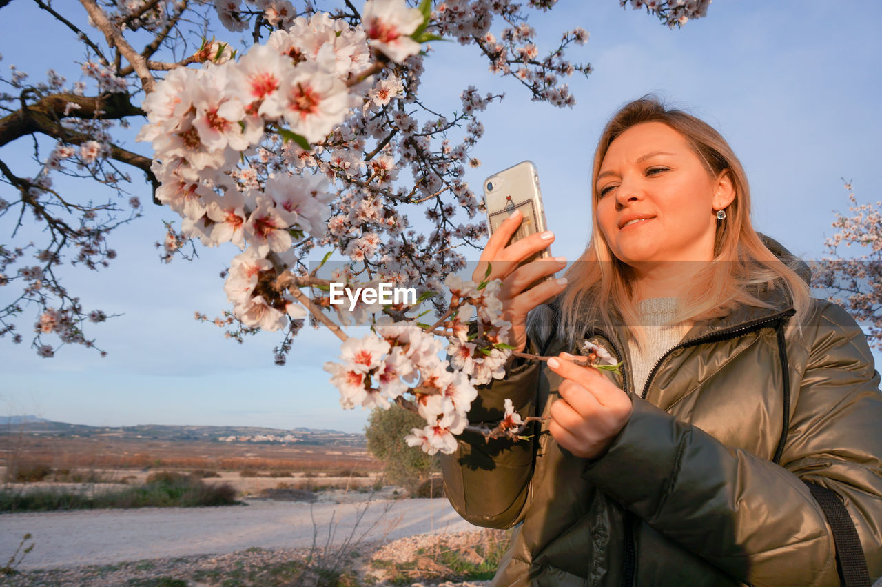 Young blond woman taking a mobile photo of almonds in blossom early morning