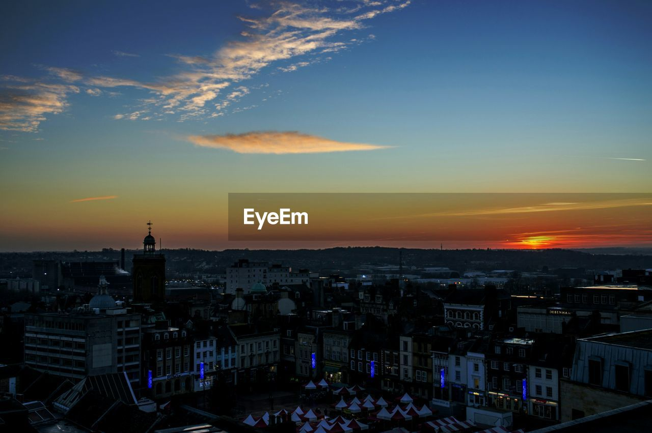 HIGH ANGLE VIEW OF CITYSCAPE AT SUNSET