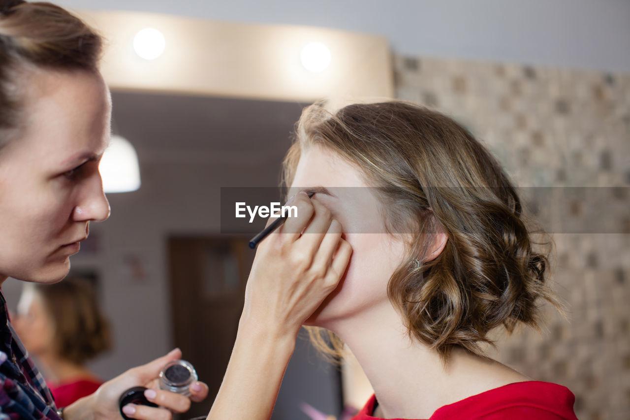 Woman applying make-up to female model at studio