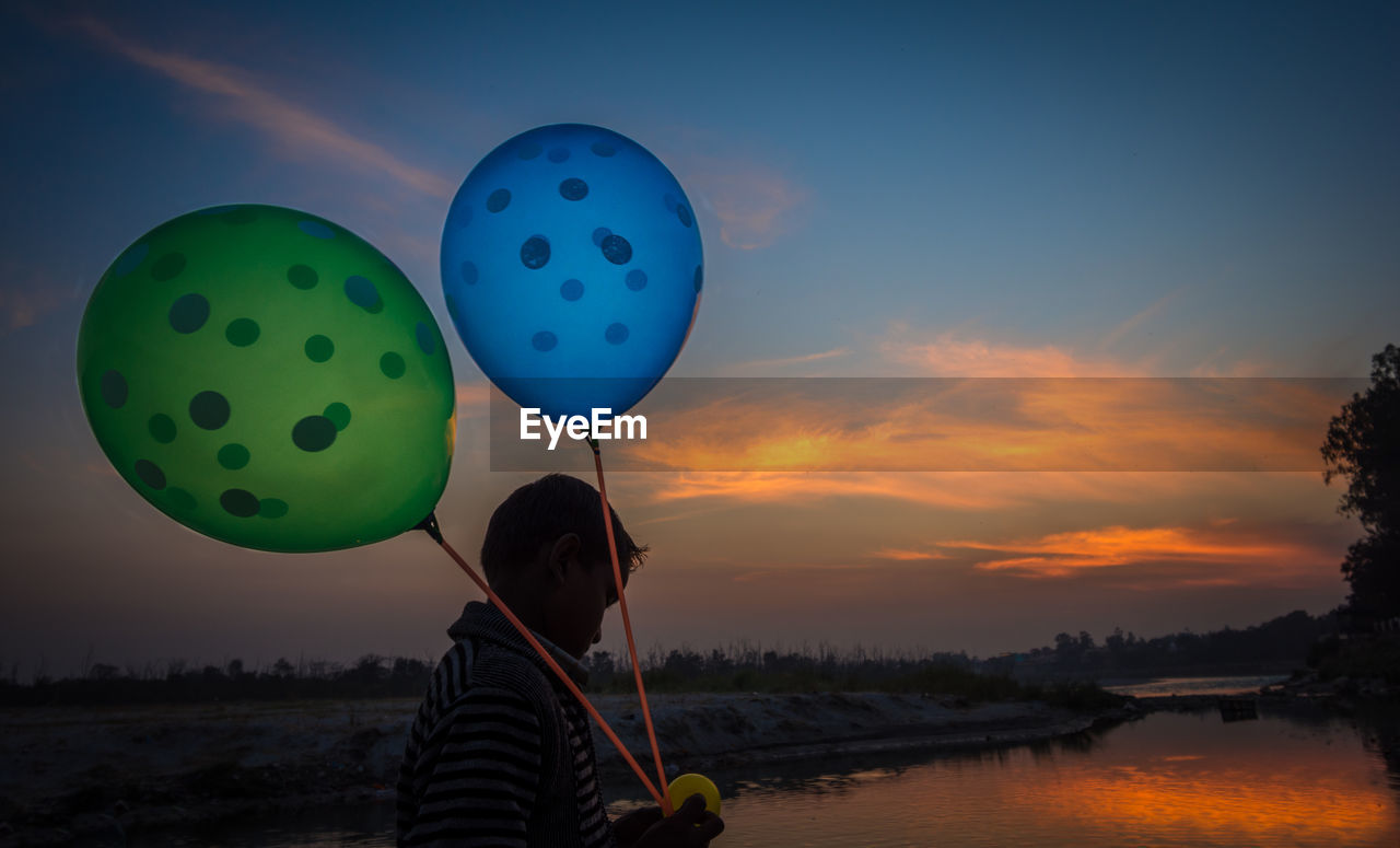 Side view of boy holding balloons against sky during sunset